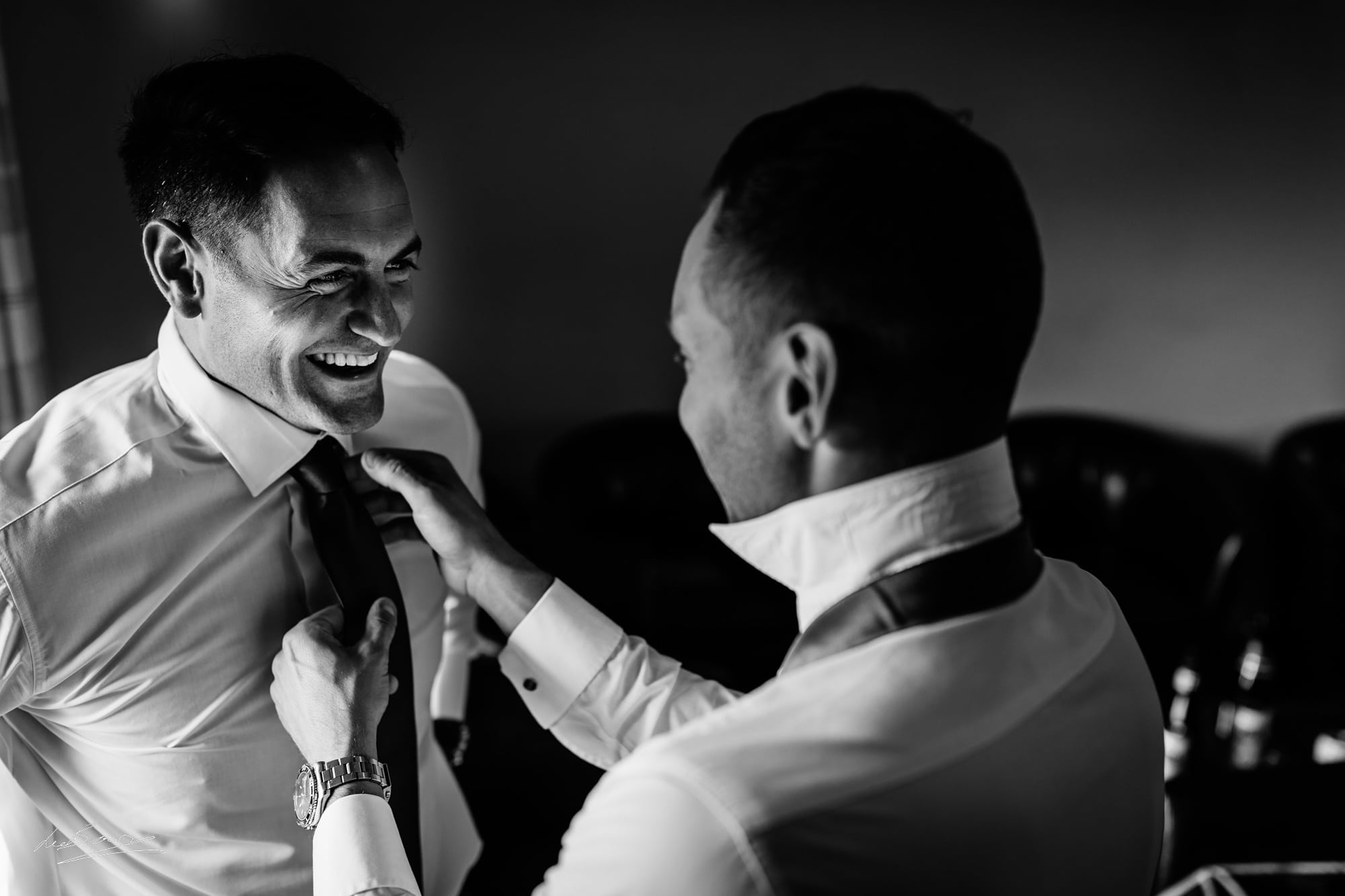 the groom having his tie done up