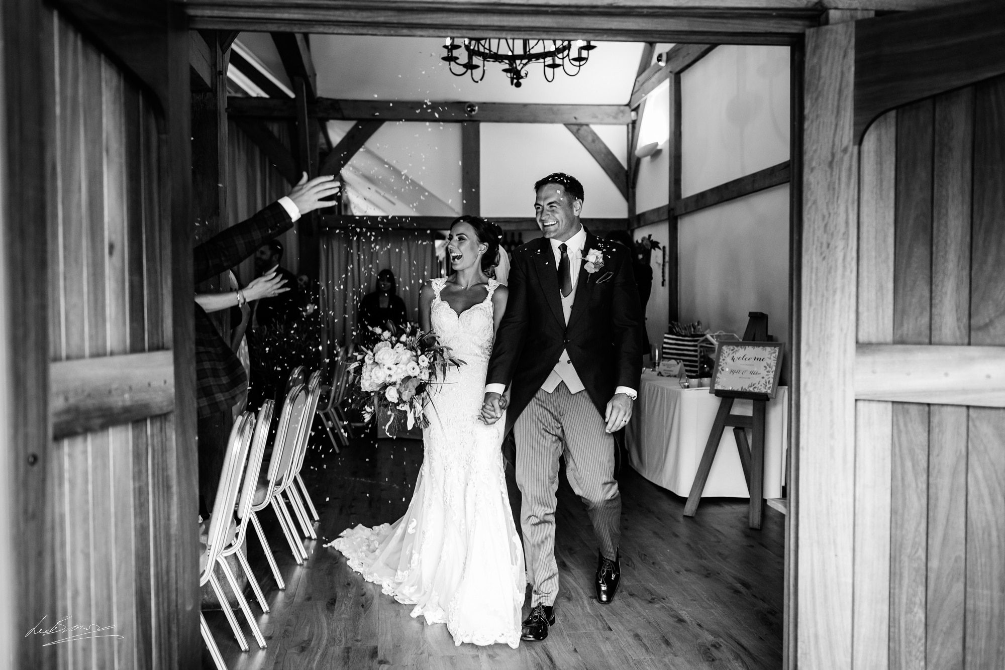 the bride and groom having confetti thrown at them at sandhole oak barn