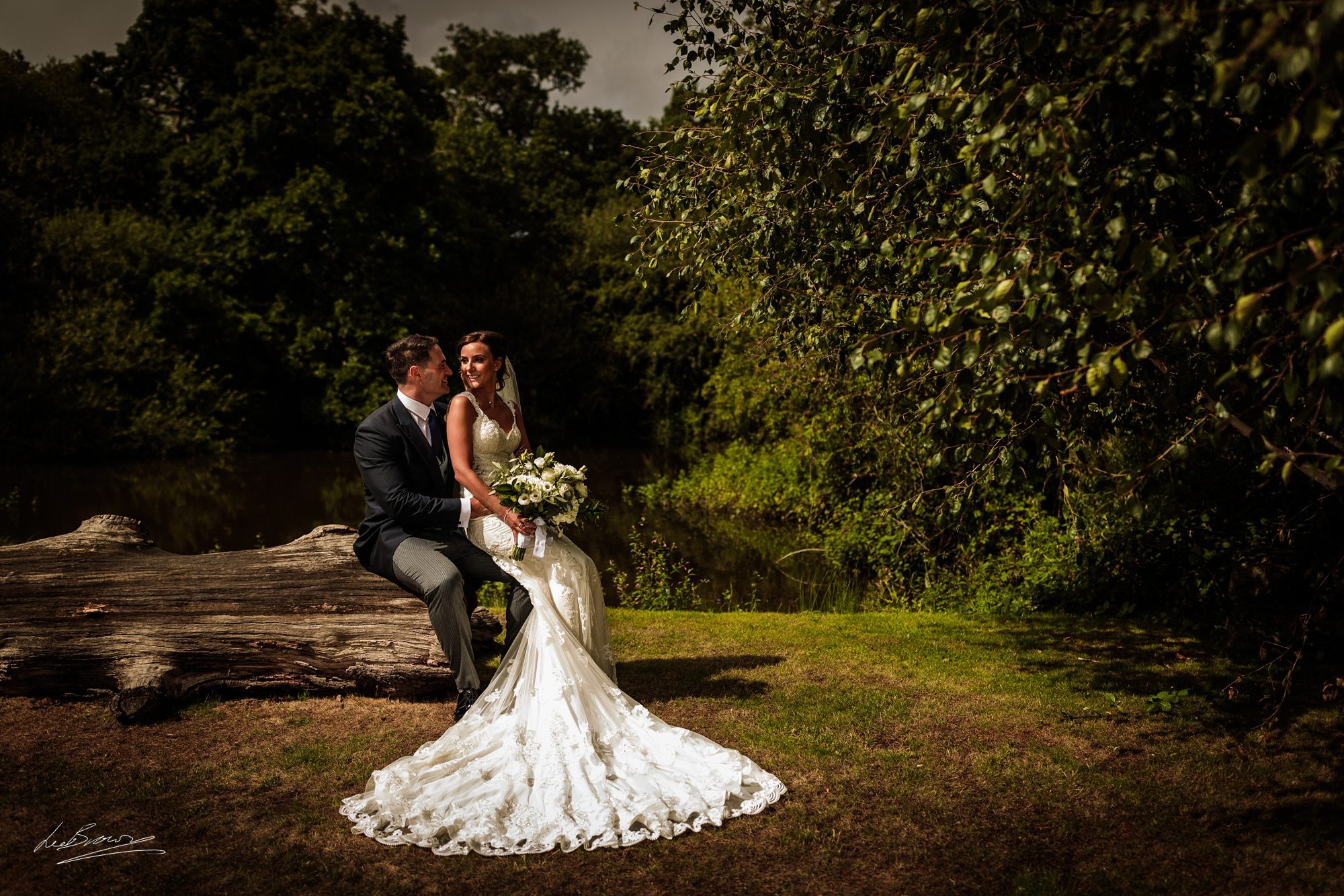 the bride sat on the grooms knee next to a pond
