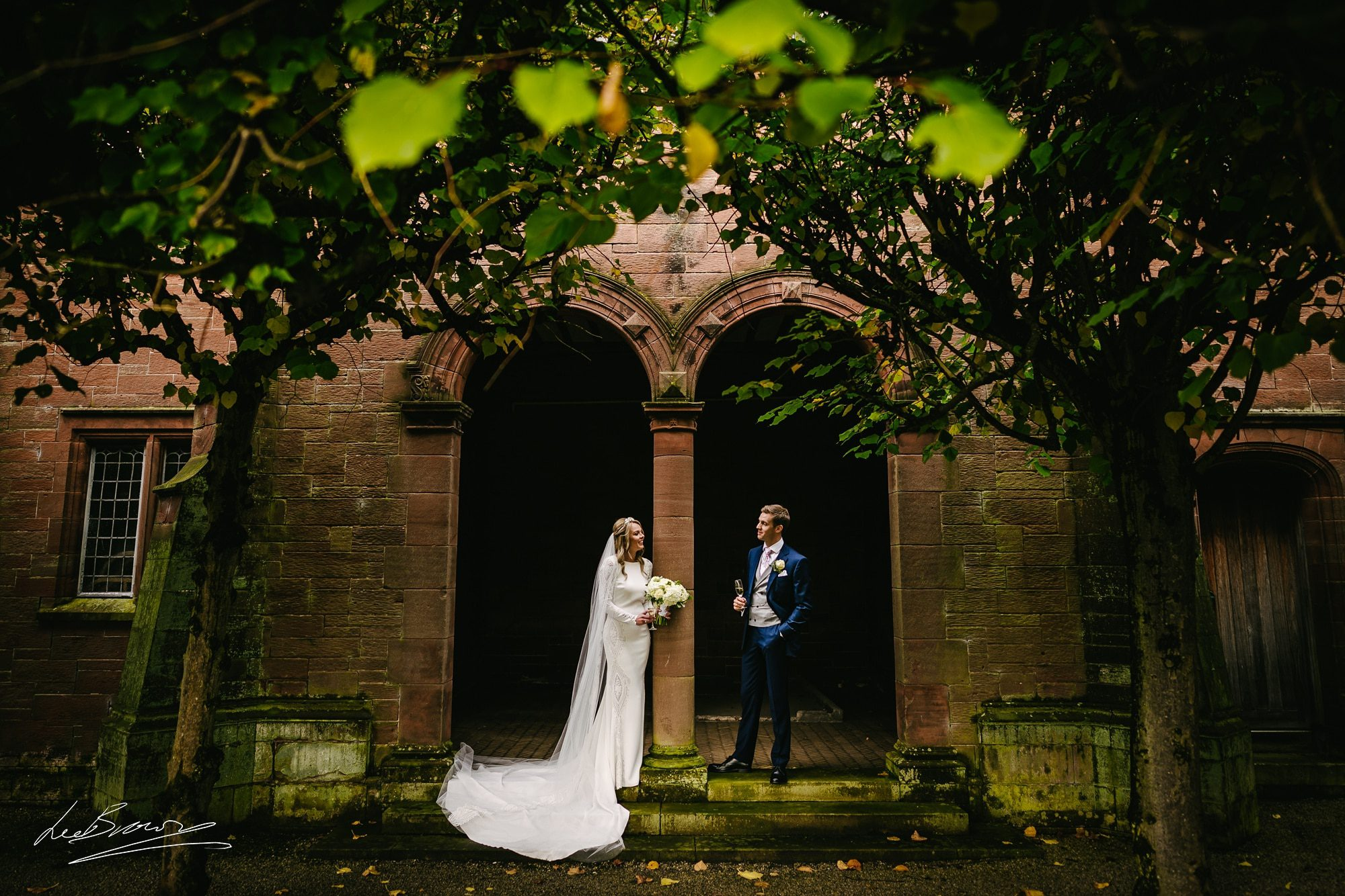 the bride and groom stood in the archway at thornton manor after their wedding ceremony