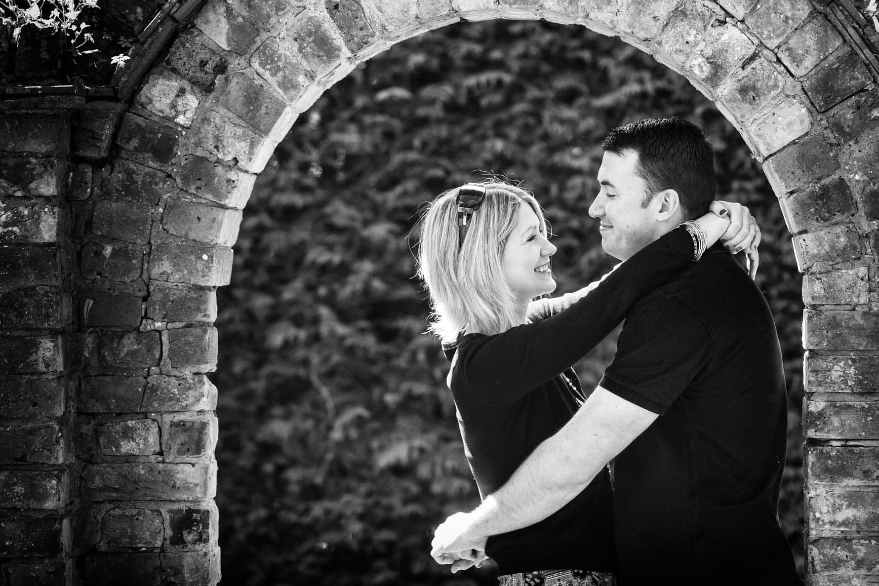 Hugging under the arch on an engagement shoot by Hertfordshire wedding photographer Graham Warrellow
