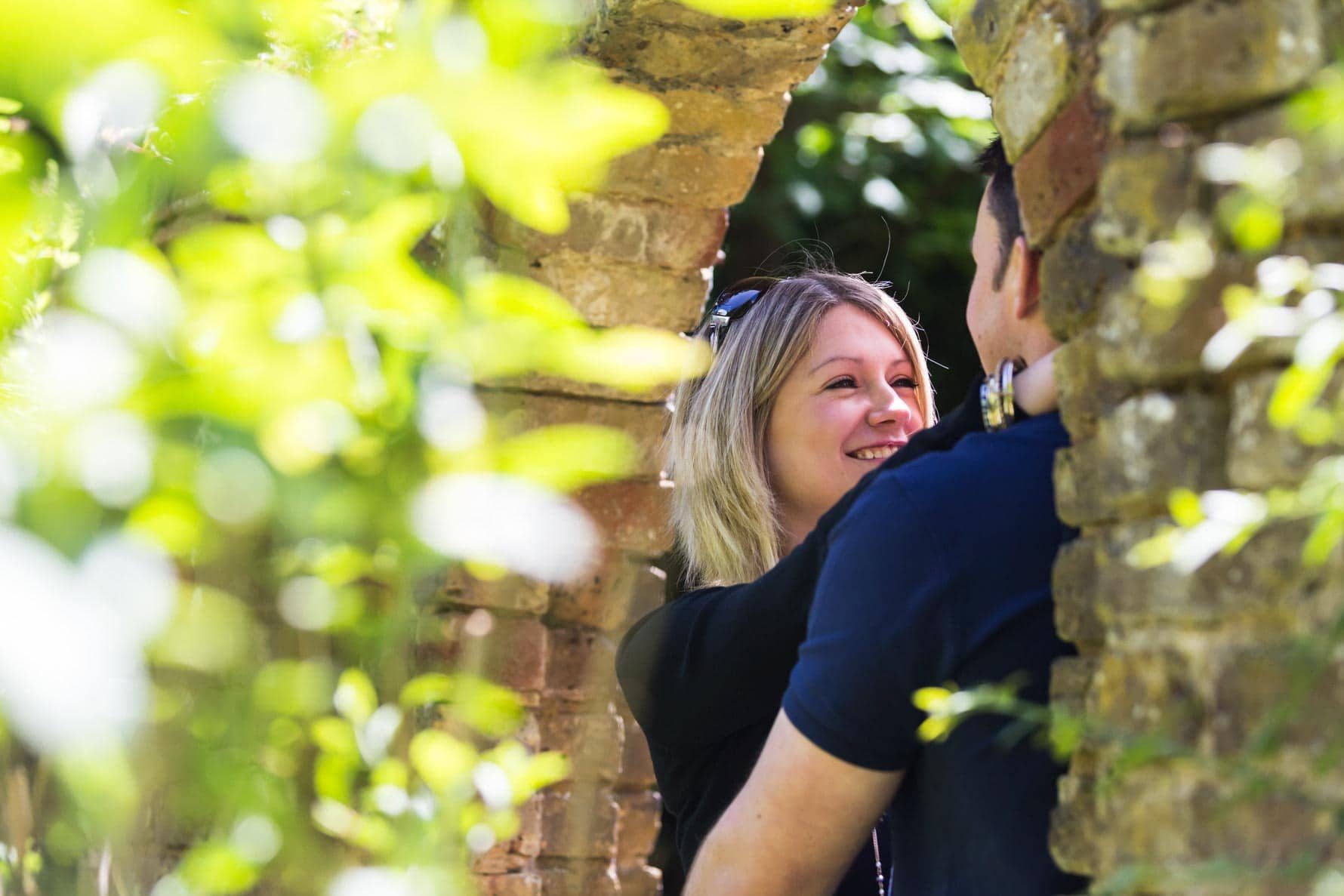 Under the arch on an engagement photoshoot by Hertfordshire wedding photographer