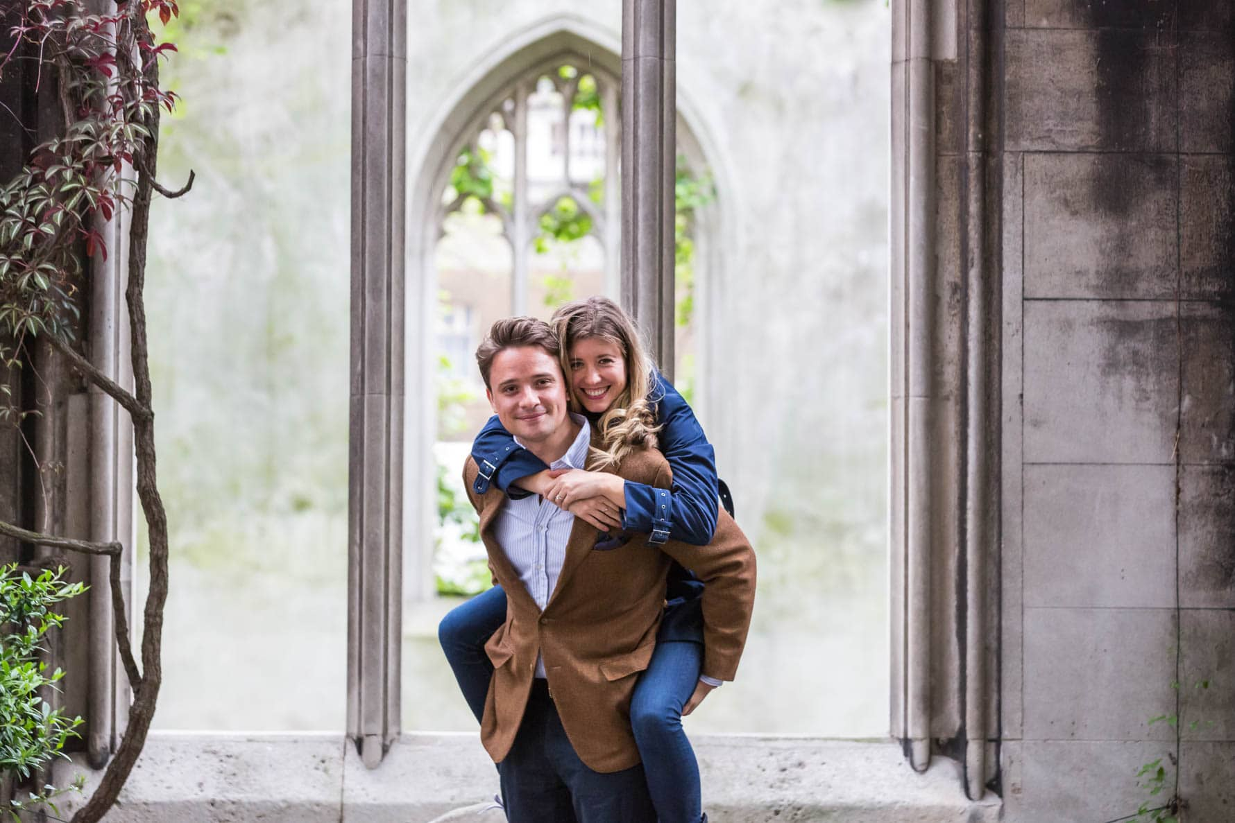 Oliver gives Paula a piggyback during their fun London engagement photoshoot in the beautiful gardens of St Dunstan-in-the-East