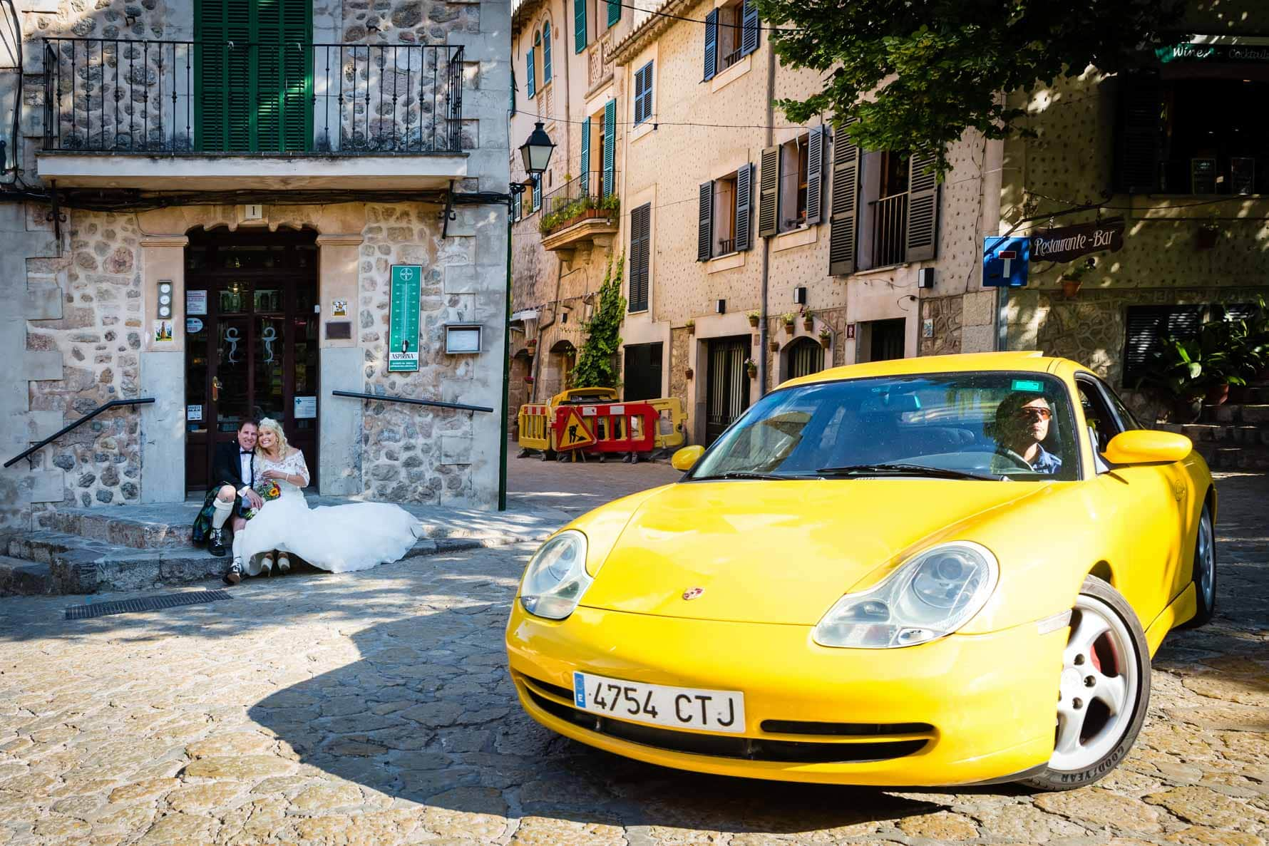 Bride and groom and yellow Porsche in Valldemossa