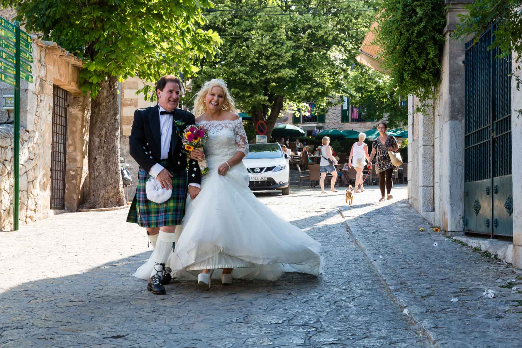 Happy bride and groom walking in Valldemossa after their Mallorca wedding