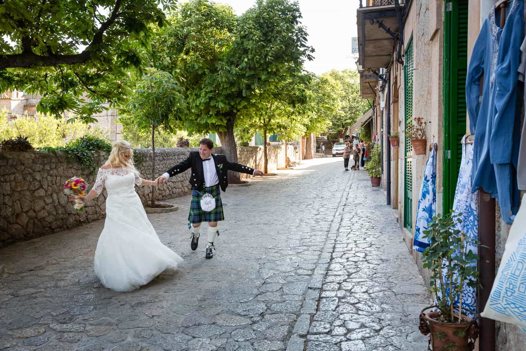 Happy bride and groom dancing in the streets of Valldemossa after their Mallorca wedding