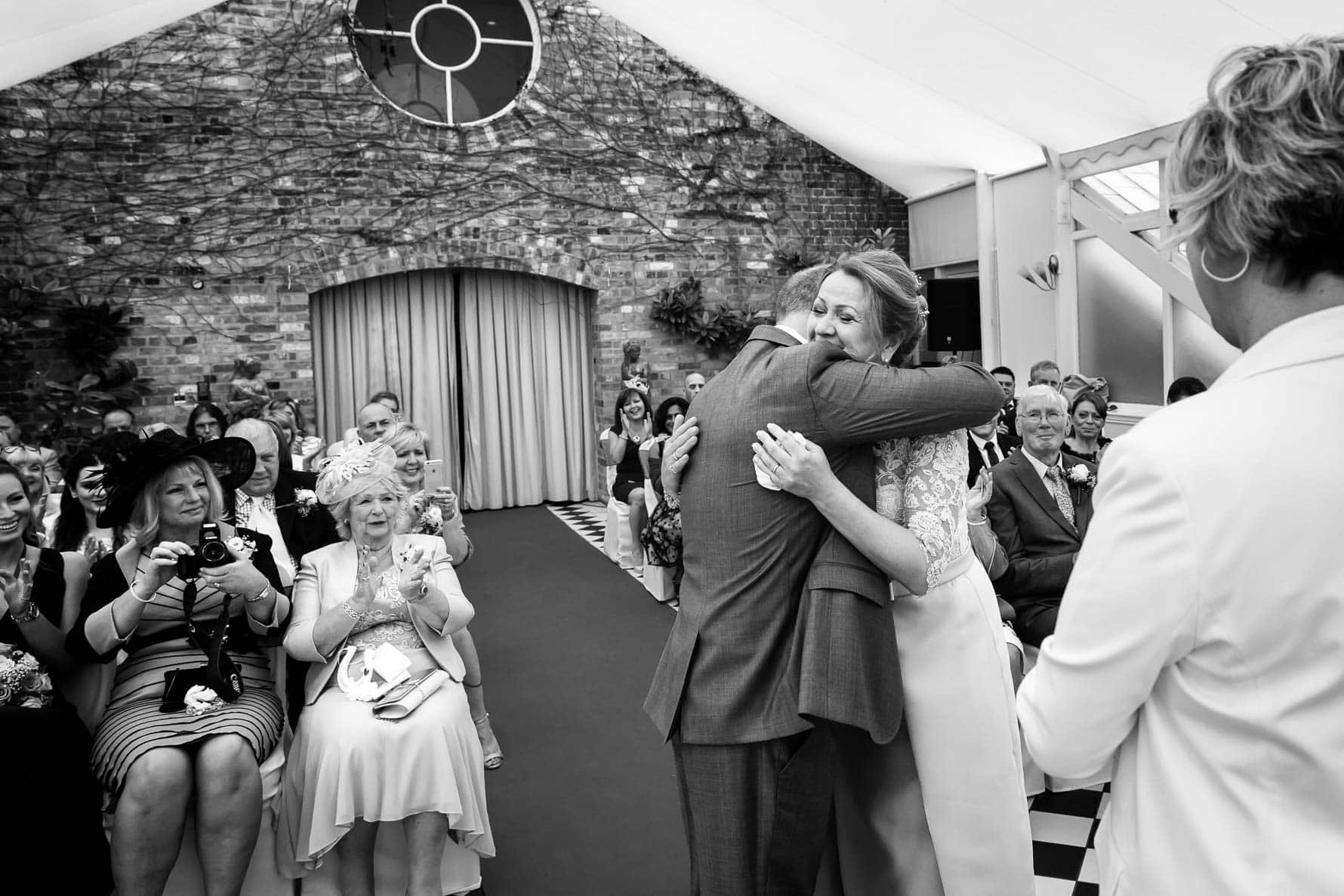First hug as a married couple at Hanbury Manor wedding by Hertfordshire wedding photographer Graham Warrellow