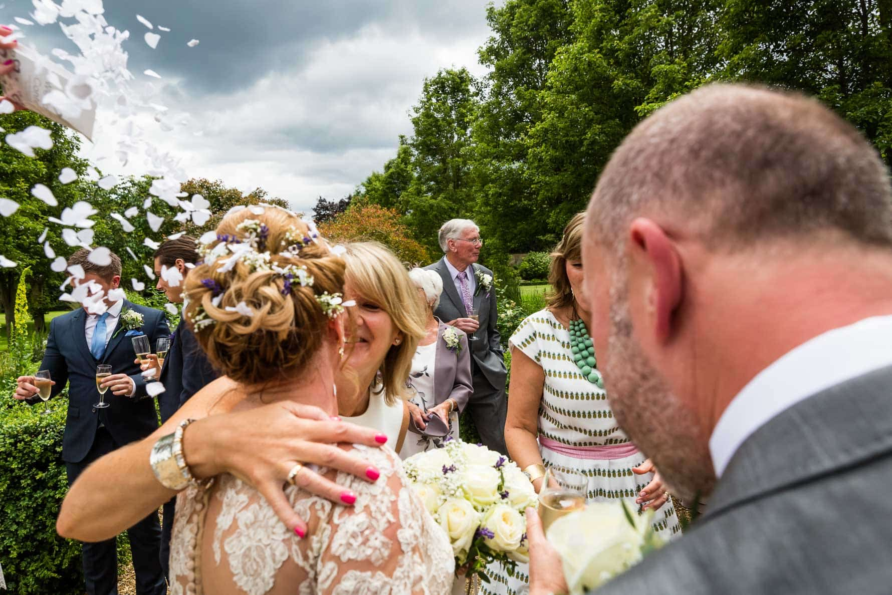 A hug and a kiss for the bride at Hanbury Manor wedding by Hertfordshire wedding photographer Graham Warrellow