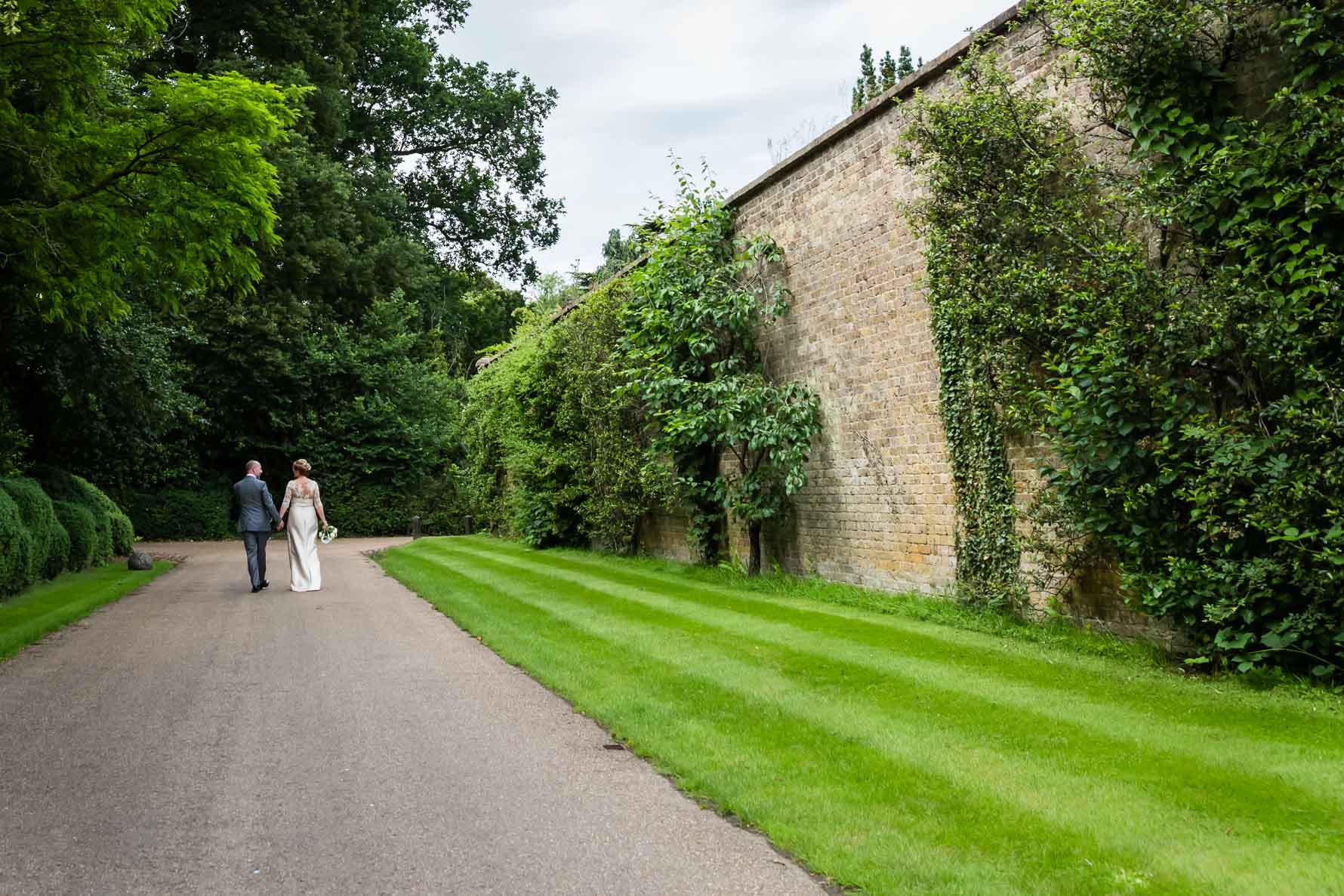 Bride and groom walking outside the Garden Court at Hanbury Manor