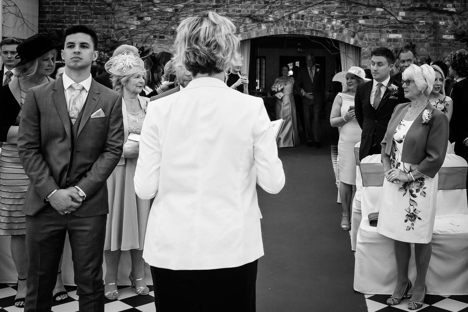 The mums look at one another as the bride enters The Garden Court at Hanbury Manor by Hertfordshire wedding photographer Graham Warrellow