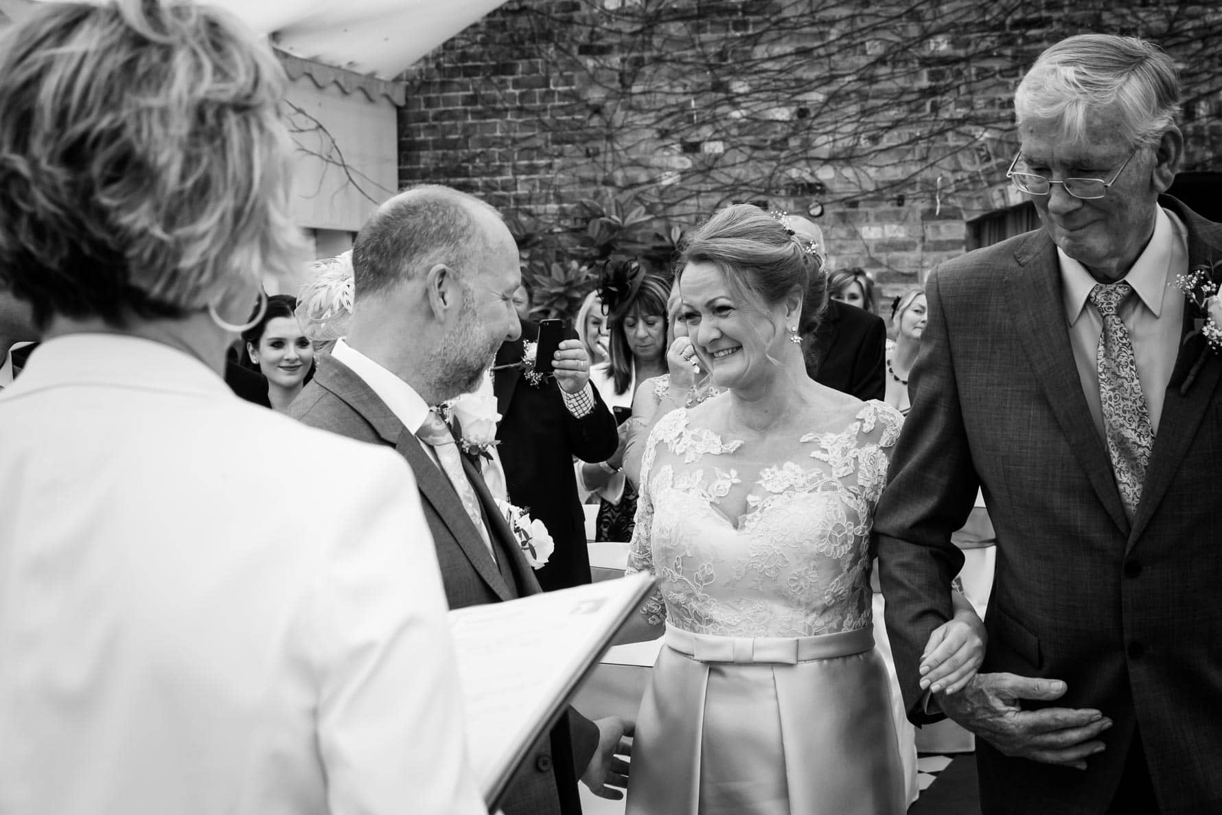 The groom greets his bride at their Hertfordshire wedding at Hanbury Manor