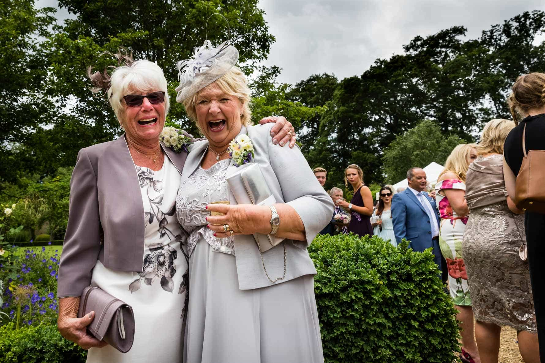 The bride and groom's mums laughing at Hanbury Manor wedding by Hertfordshire wedding photographer Graham Warrellow