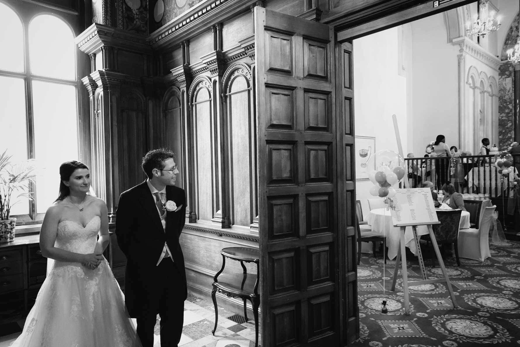 Bride and groom peek in to the Romanov Room at Luton Hoo Hotel in Bedfordshire