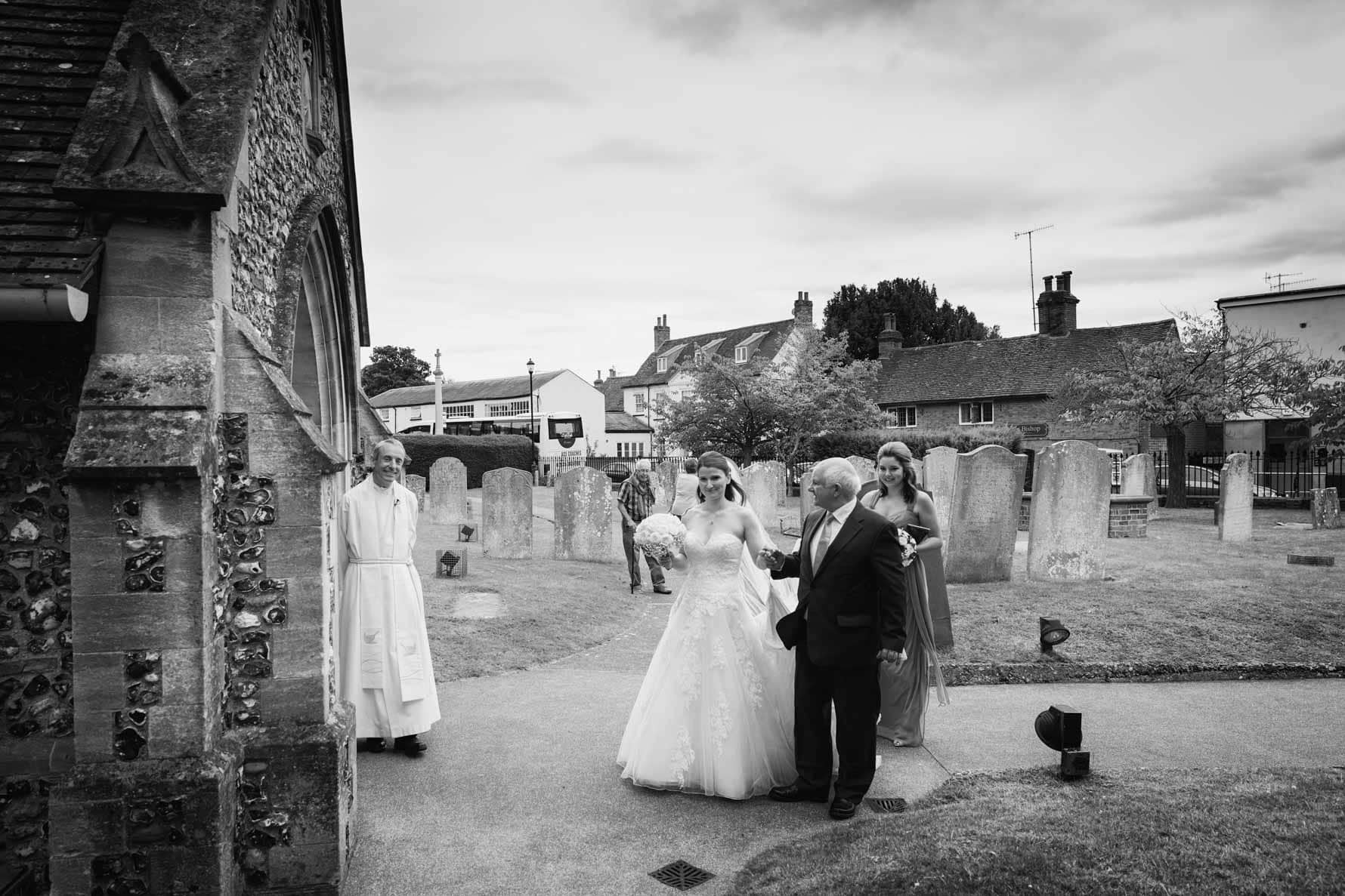 Vicar greets bridal party at St Mary's Church, Welwyn, Hertfordshire