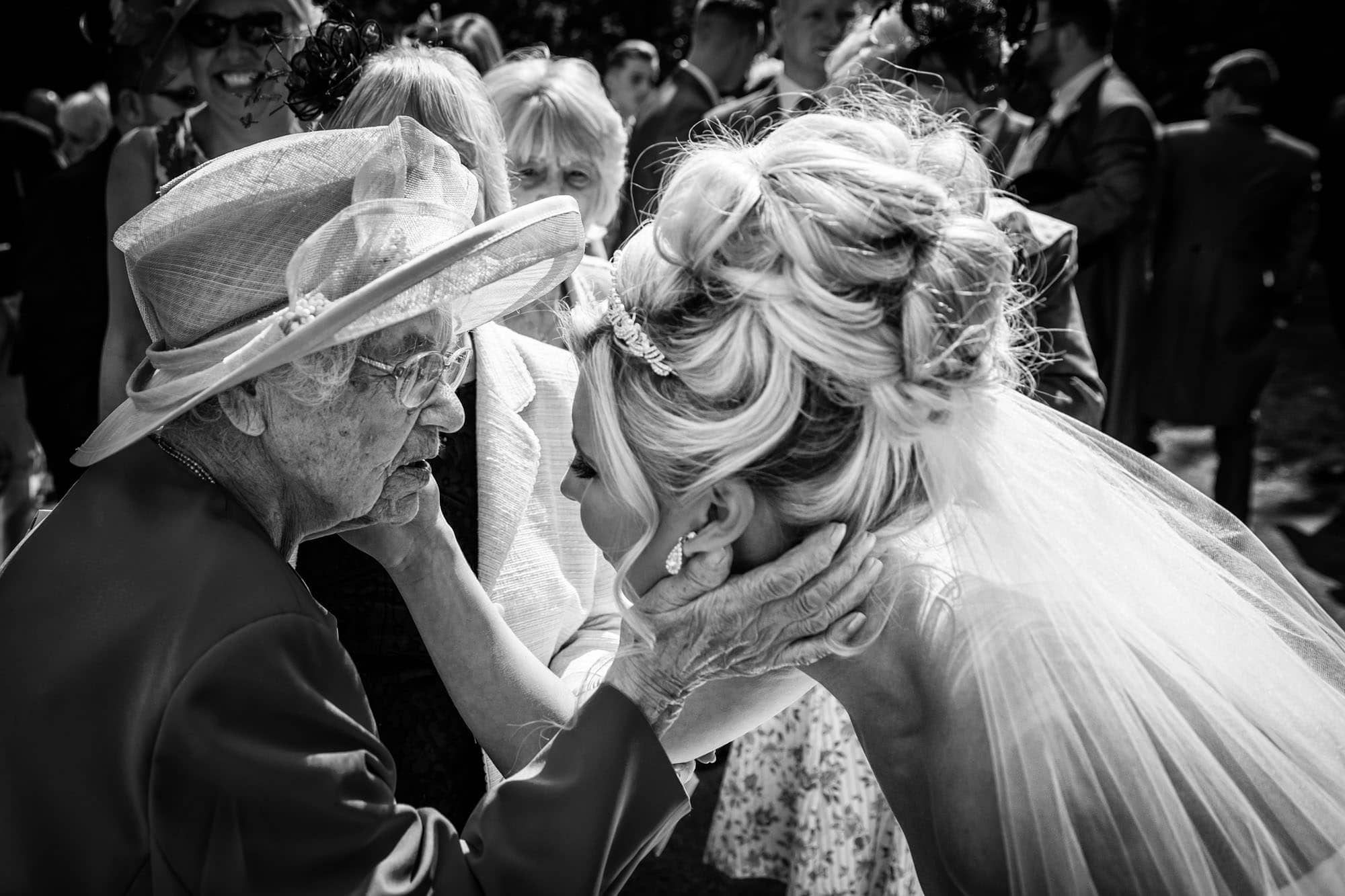 An example of documentary wedding photography as a bride and 104 year old great grandmother touch faces.