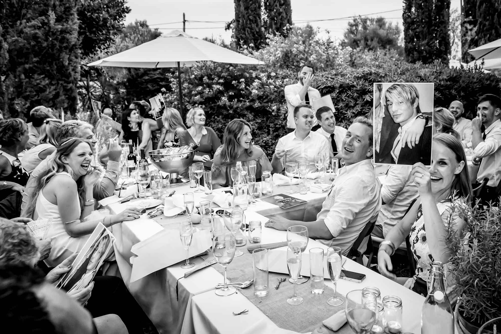 Photos of the groom are passed around during the best man's speech at the finca wedding captured by Mallorca wedding photographer Graham Warrellow