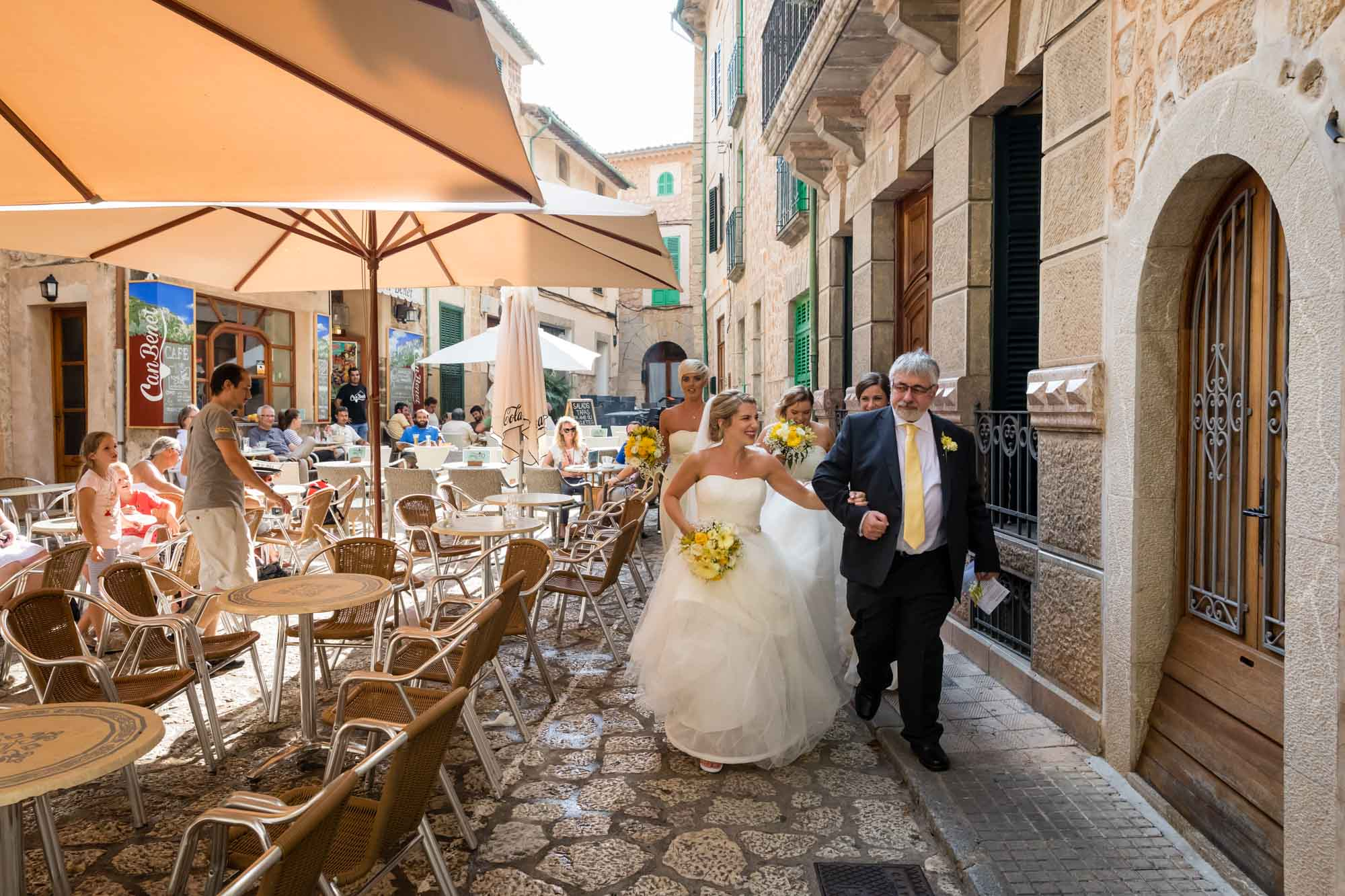 Bridal party passing cafes for wedding at Fornalutx church by destination wedding photographer Graham Warrellow