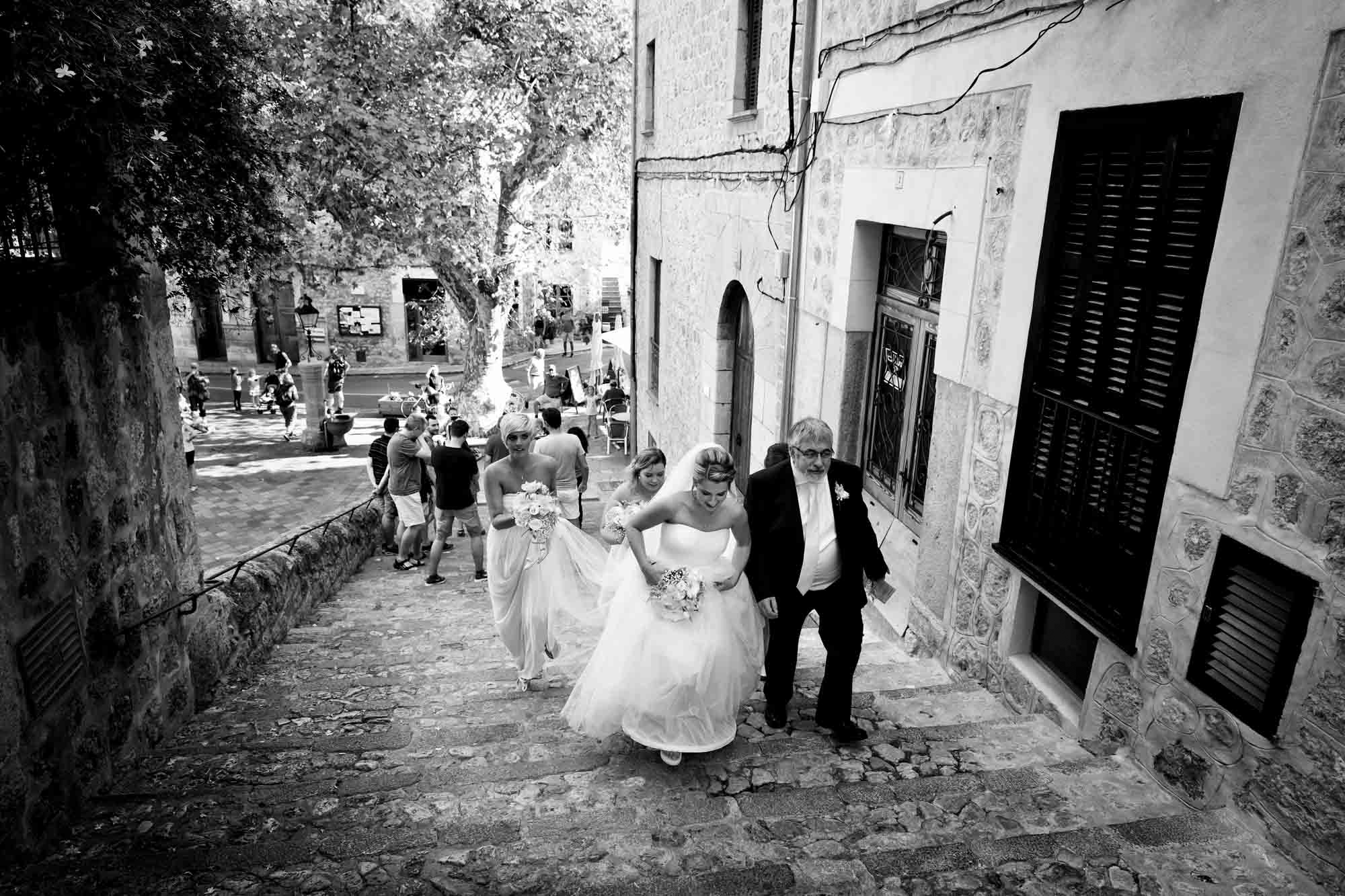 The bridal party walk up the steps to the church in Fornalutx