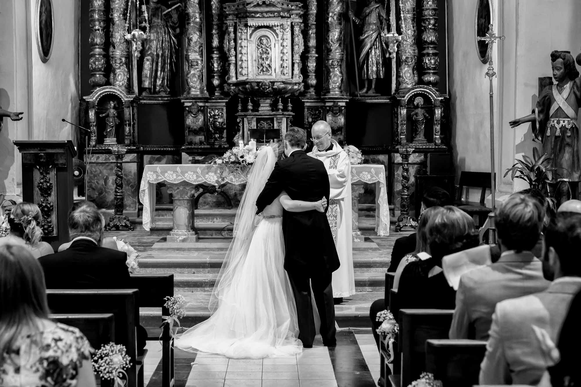 The bride and groom hug after their wedding at the church in Fornalutx, Mallorca