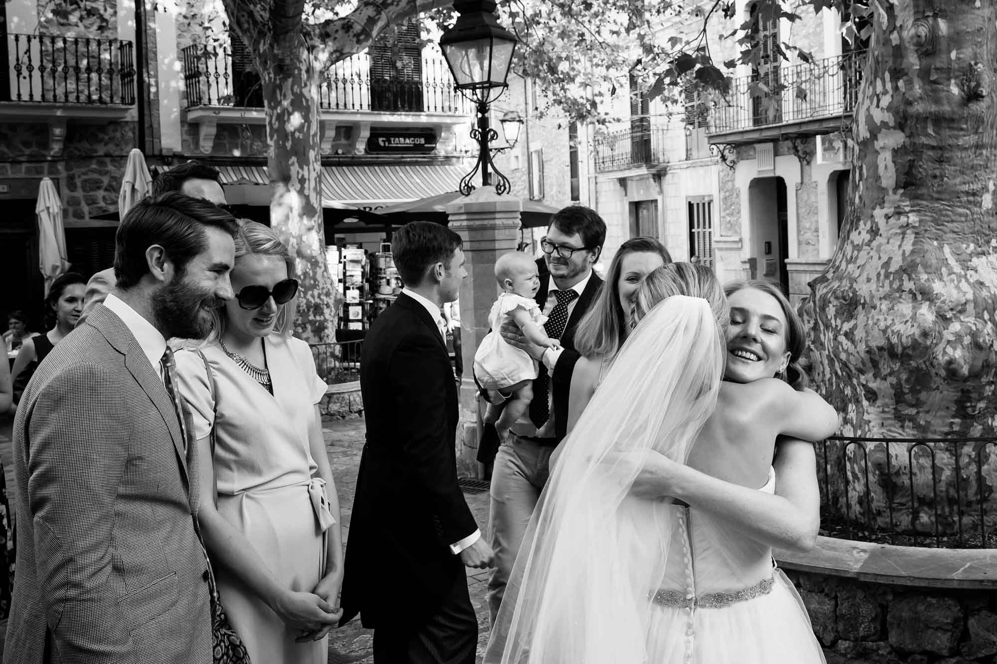 The bride hugs guests in the Plaza Major in Fornalutx, Mallorca