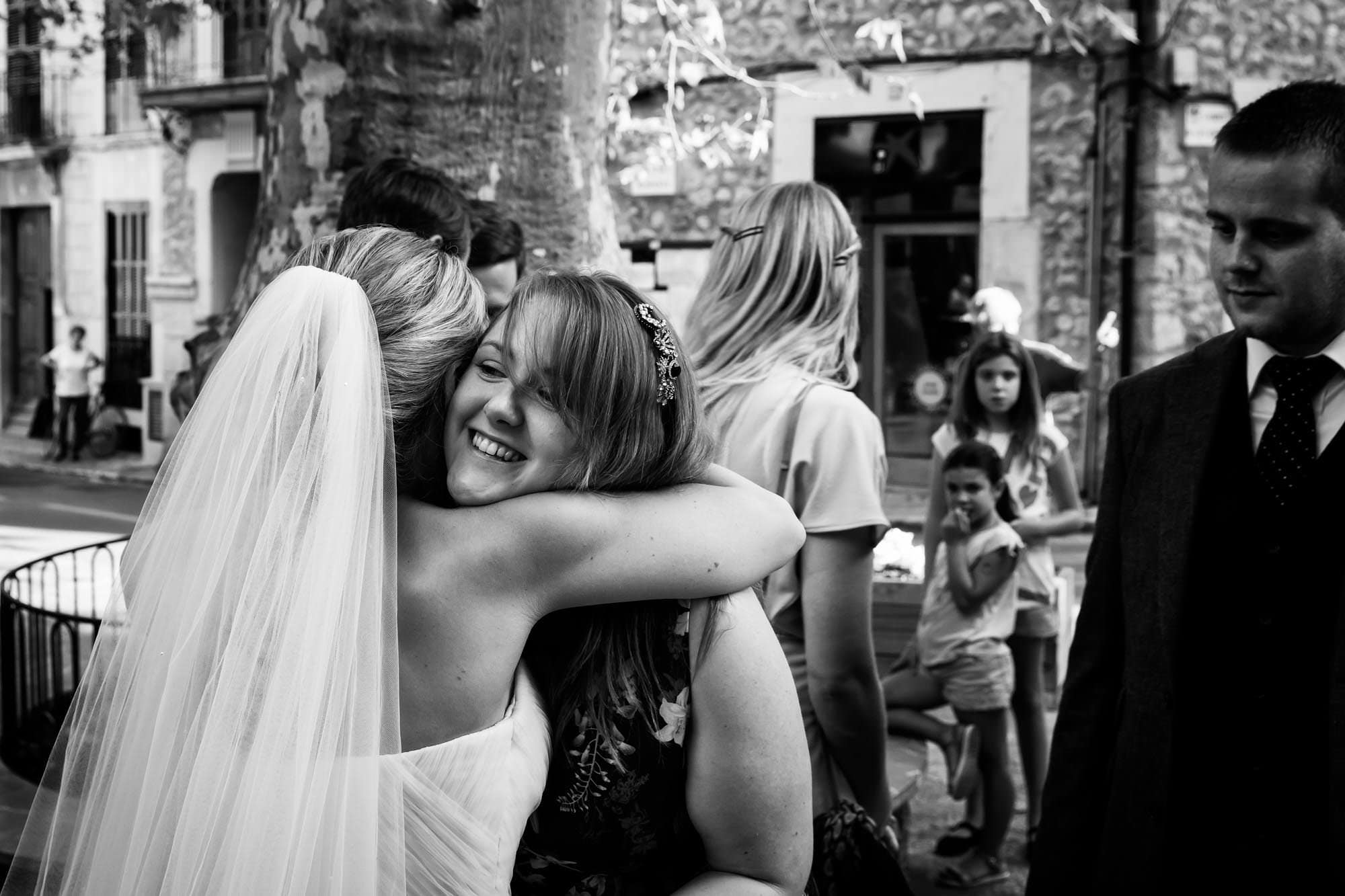 The bride hugs guests in the main square in Fornalutx