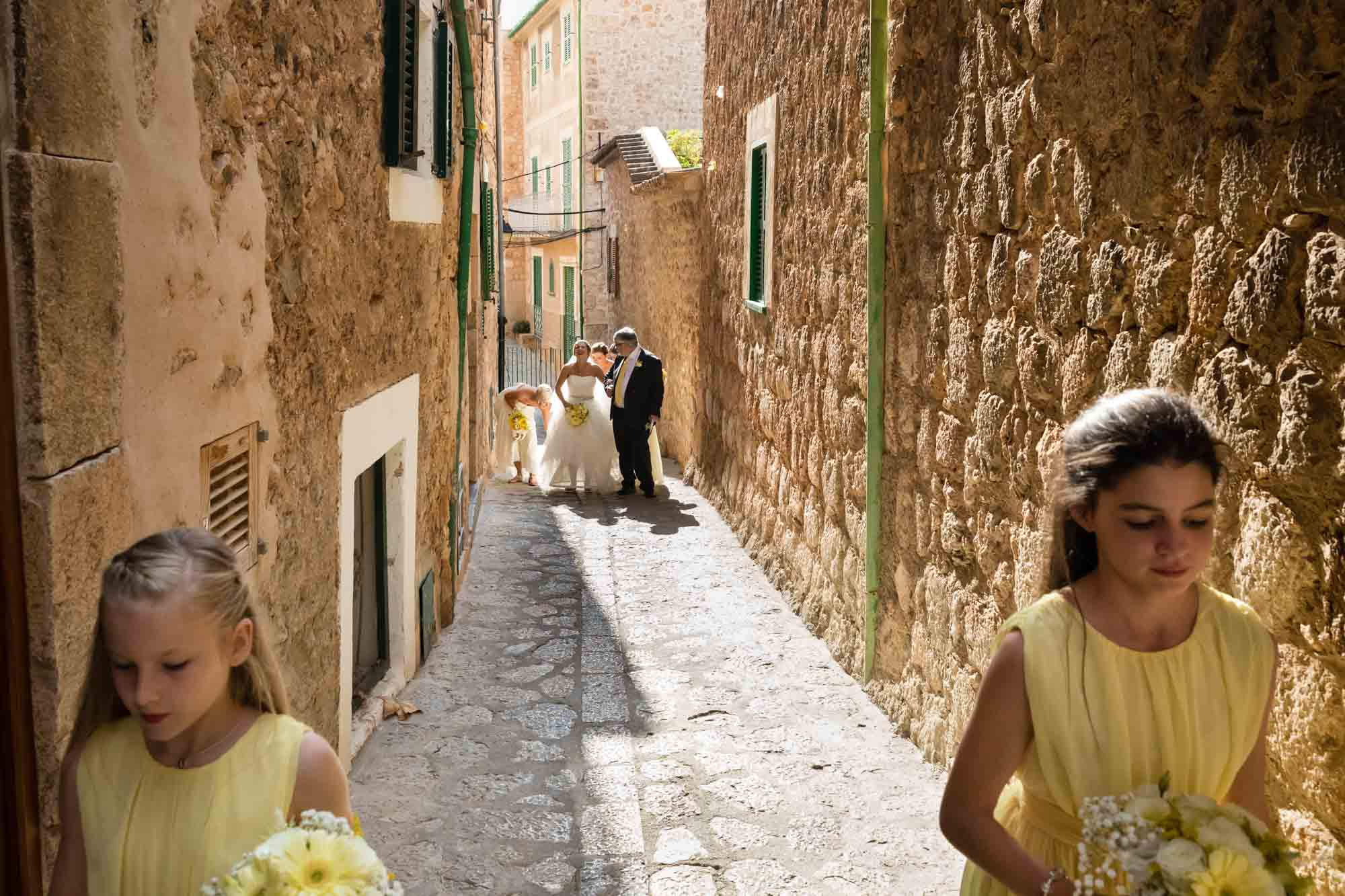 The bridal party walk along the narrow streets of Fornalutx, Mallorca
