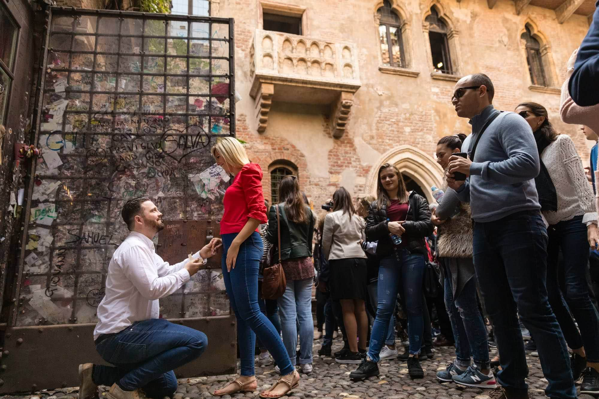 He goes down on one knee to propose marriage to his girlfriend at Casa di Giulietta in Verona
