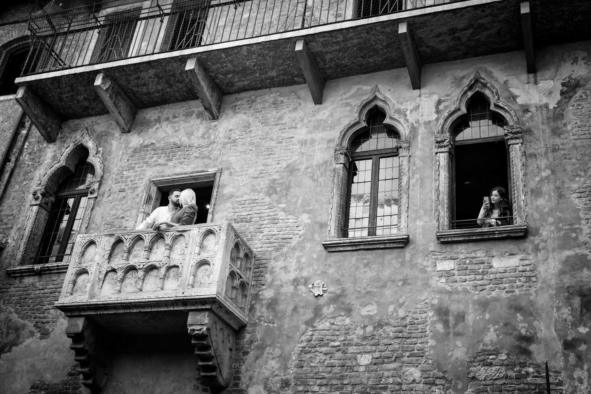 Engaged couple kiss on the Romeo and Juliet balcony in Verona, Italy