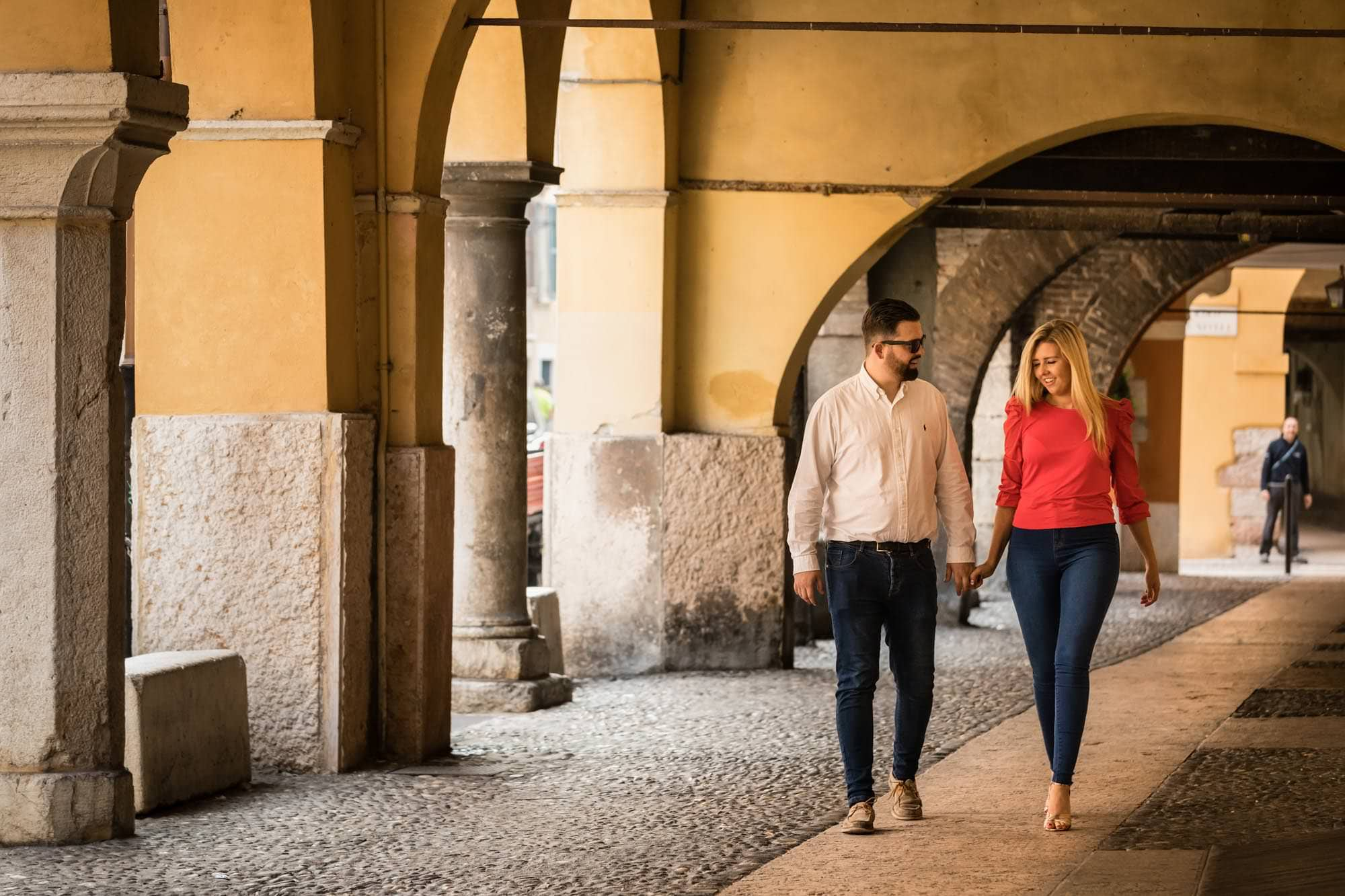 Engaged couple walking under the arches in Verona old town