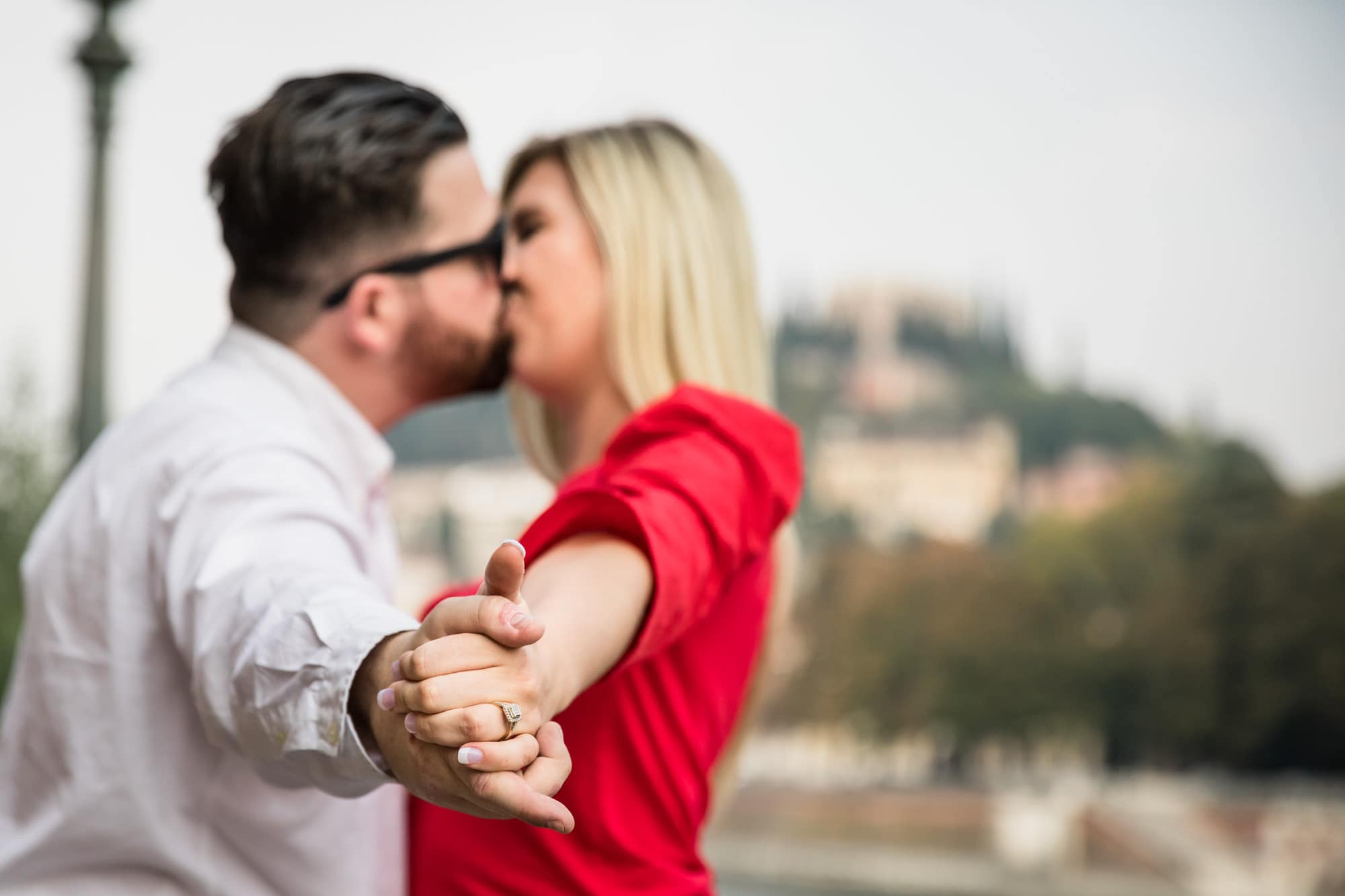 Engaged couple kissing beside the River Adige in Verona, Italy