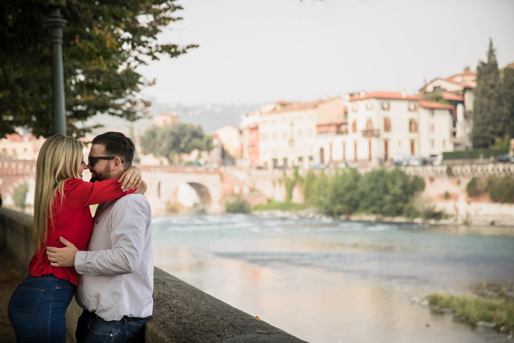 Engaged couple cuddle beside the River Adige in Verona, Italy