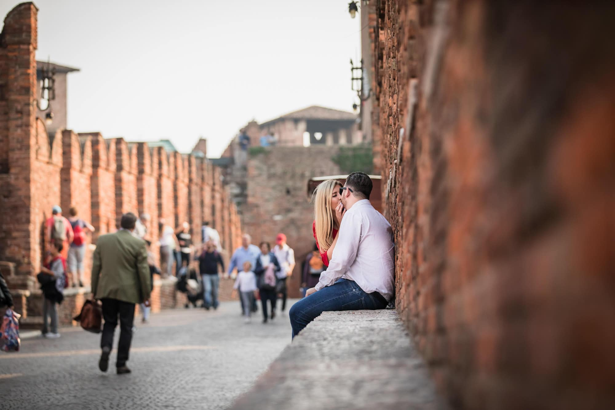 Engaged couple kissing on the Ponte Scaligero in Verona, Italy