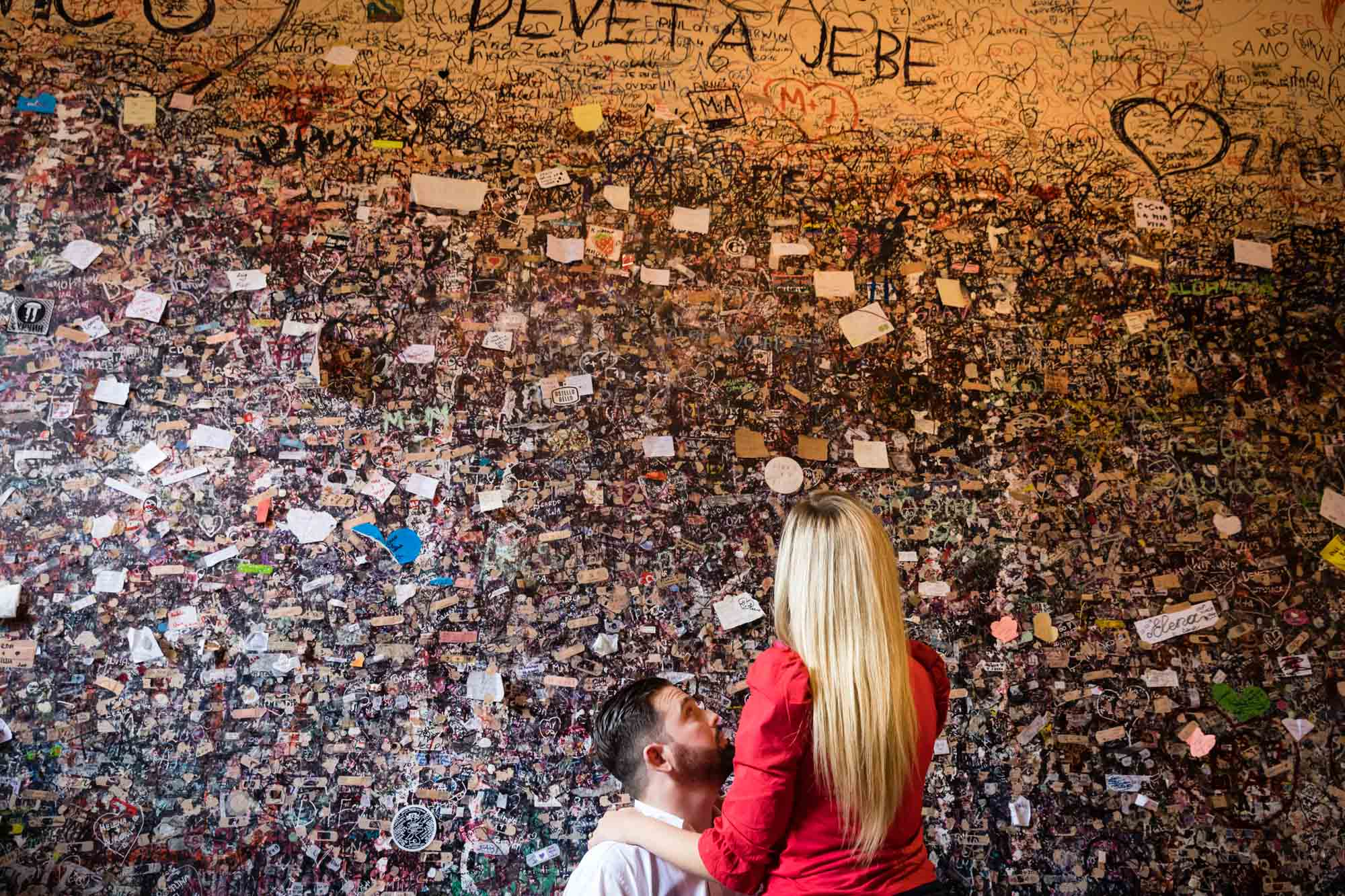 A couple in love look at the wall of love messages on the walls at Casa di Giulietta in Verona