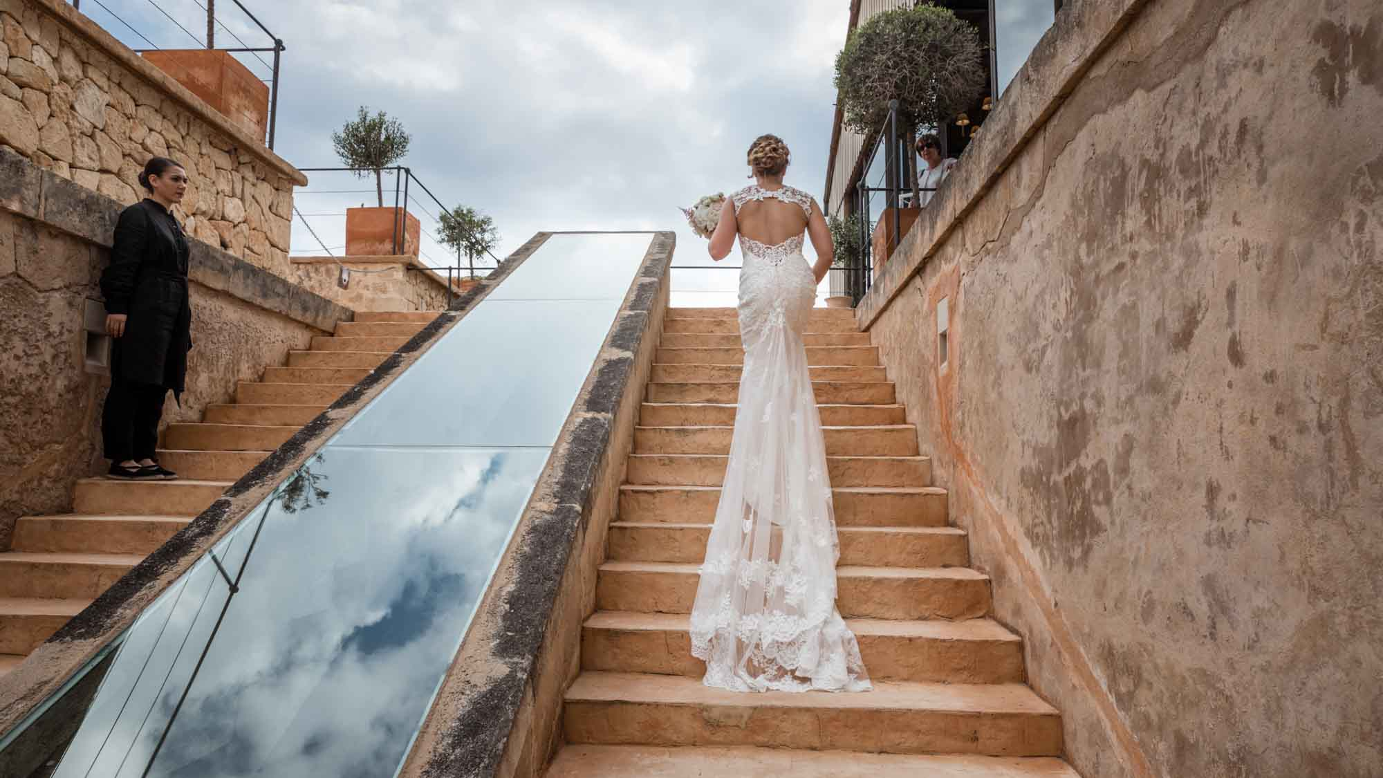 The bride ascends the stairs before her wedding reception at Cap Rocat