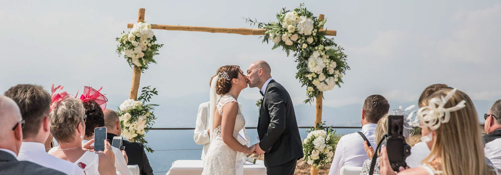 Overlooking the Mediterranean the bride and groom enjoy a first kiss after their Cap Rocat wedding