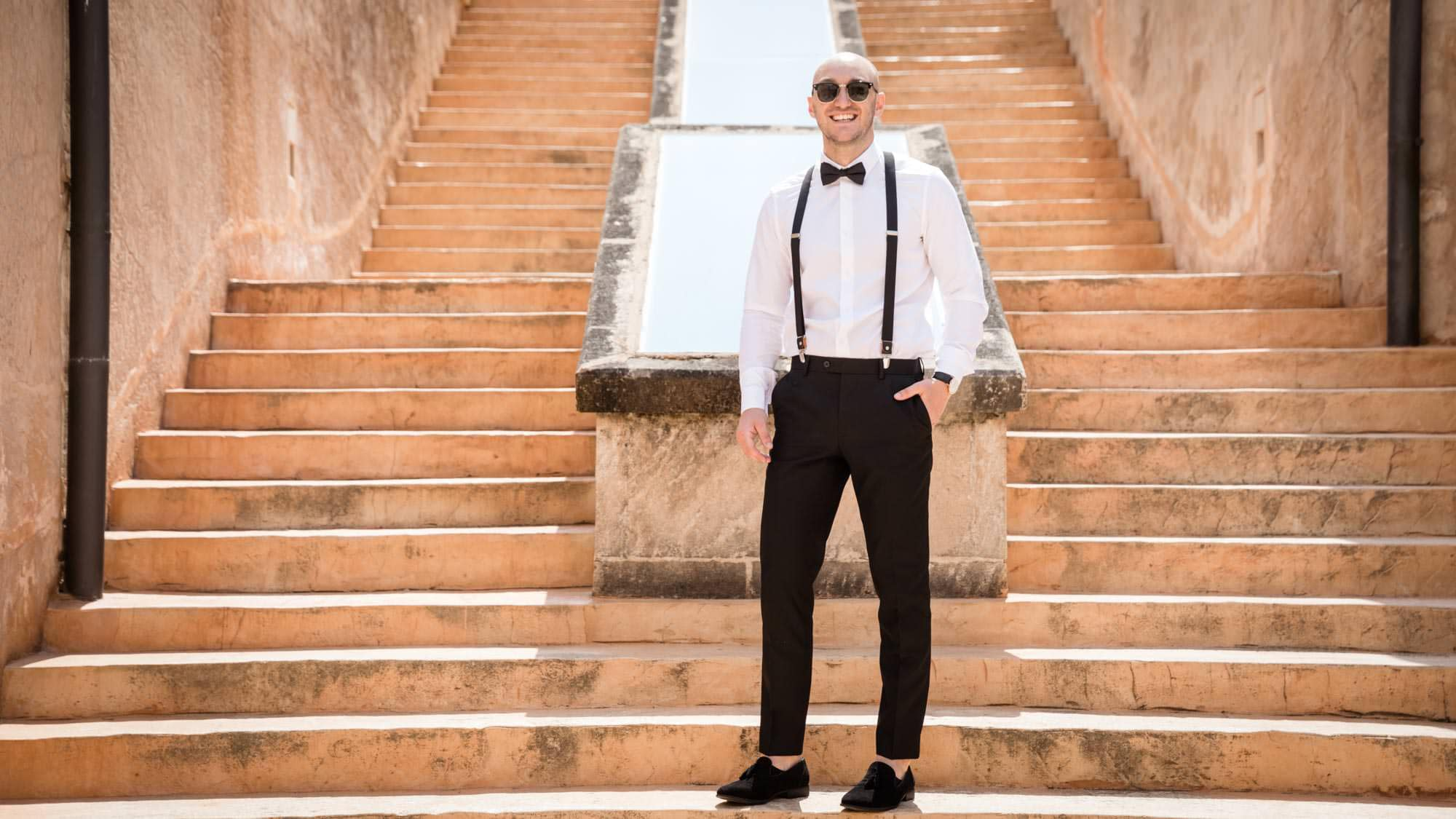 The groom poses on the steps before his wedding