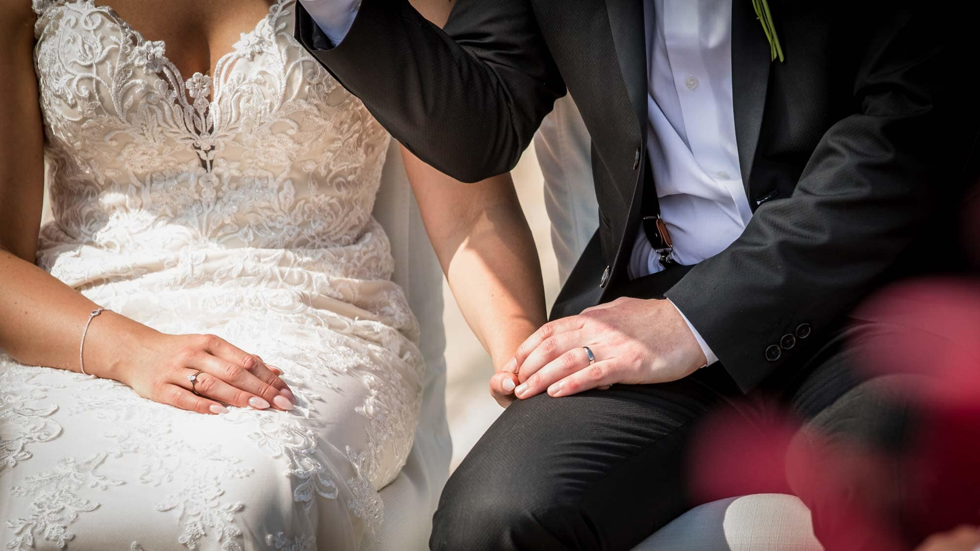 Bride and groom hold hands during their beautiful wedding ceremony