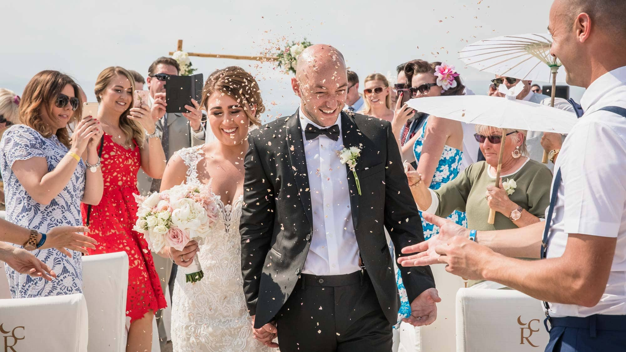 With confetti flying the happy couple after their Cap Rocat wedding in Mallorca