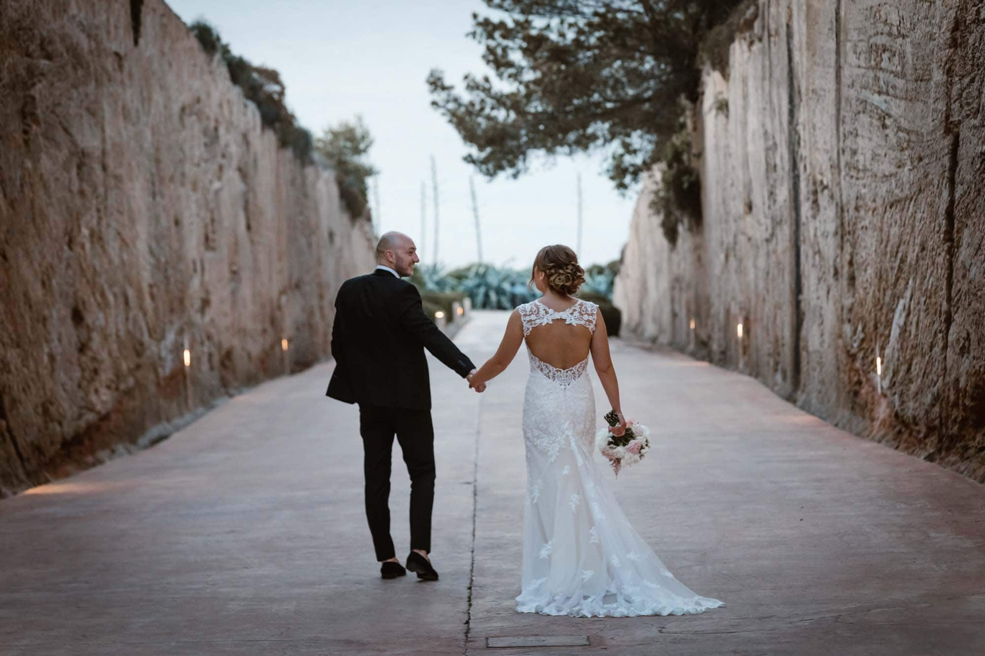 Bride and groom walk to the sea at Cap Rocat after their Mallorca wedding