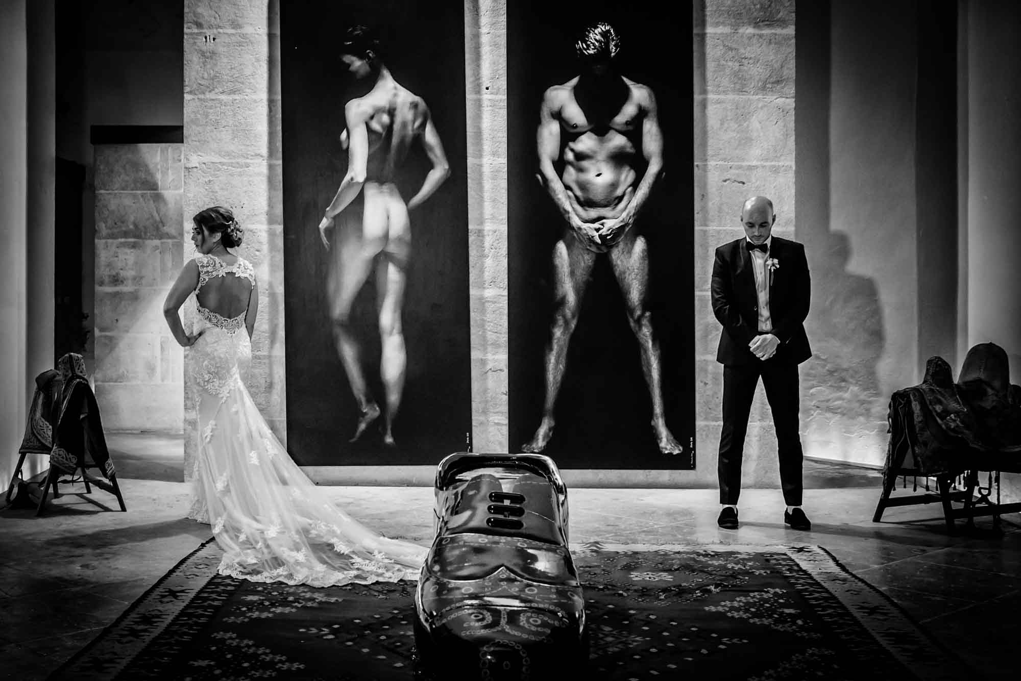 Bride and groom pose with naked man and woman and shoe at Cap Rocat