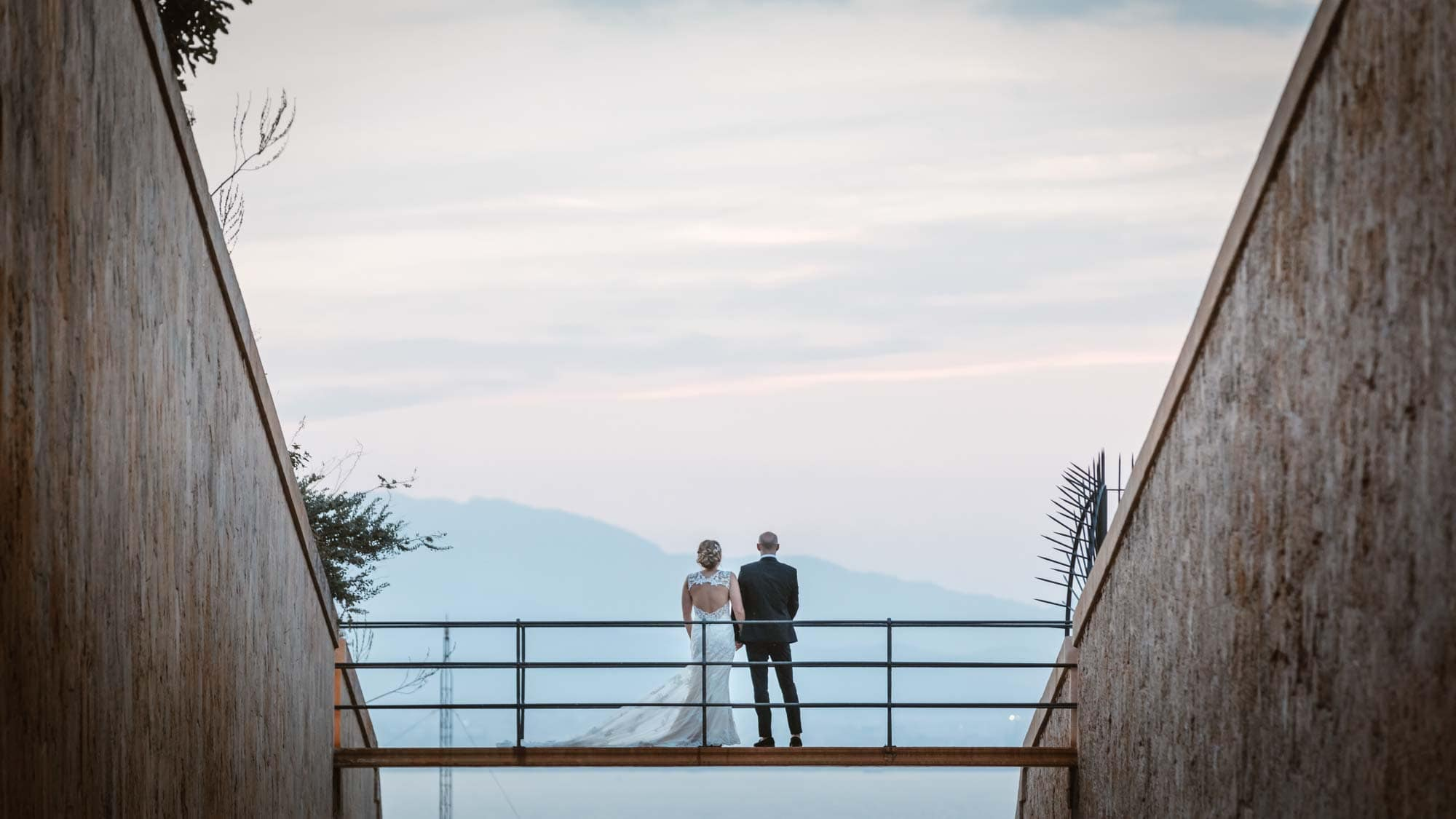 Bride and groom look out to sea from the bridge at Cap Rocat in Mallorca
