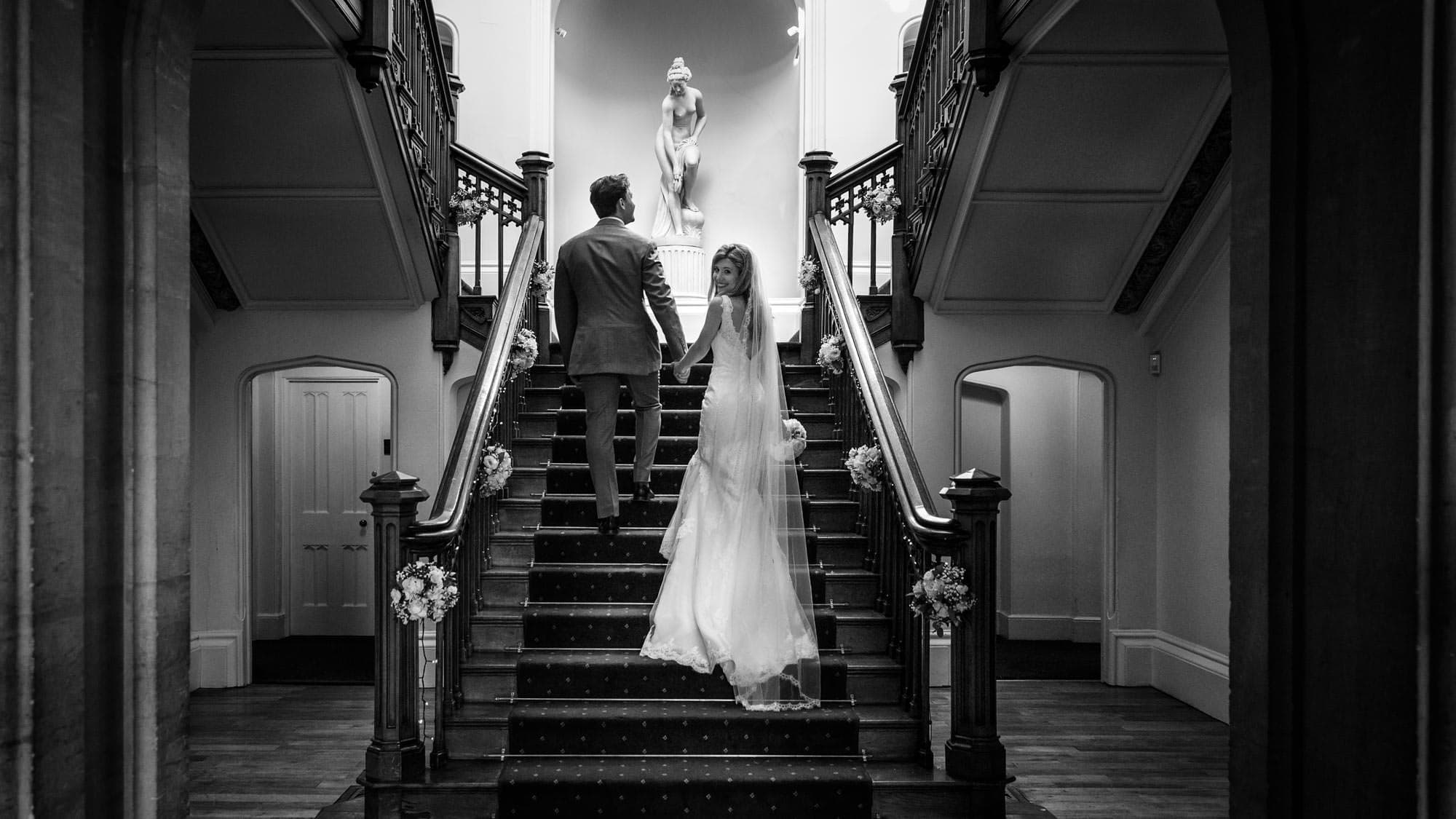 Bride and groom climb staircase at St Audries Park