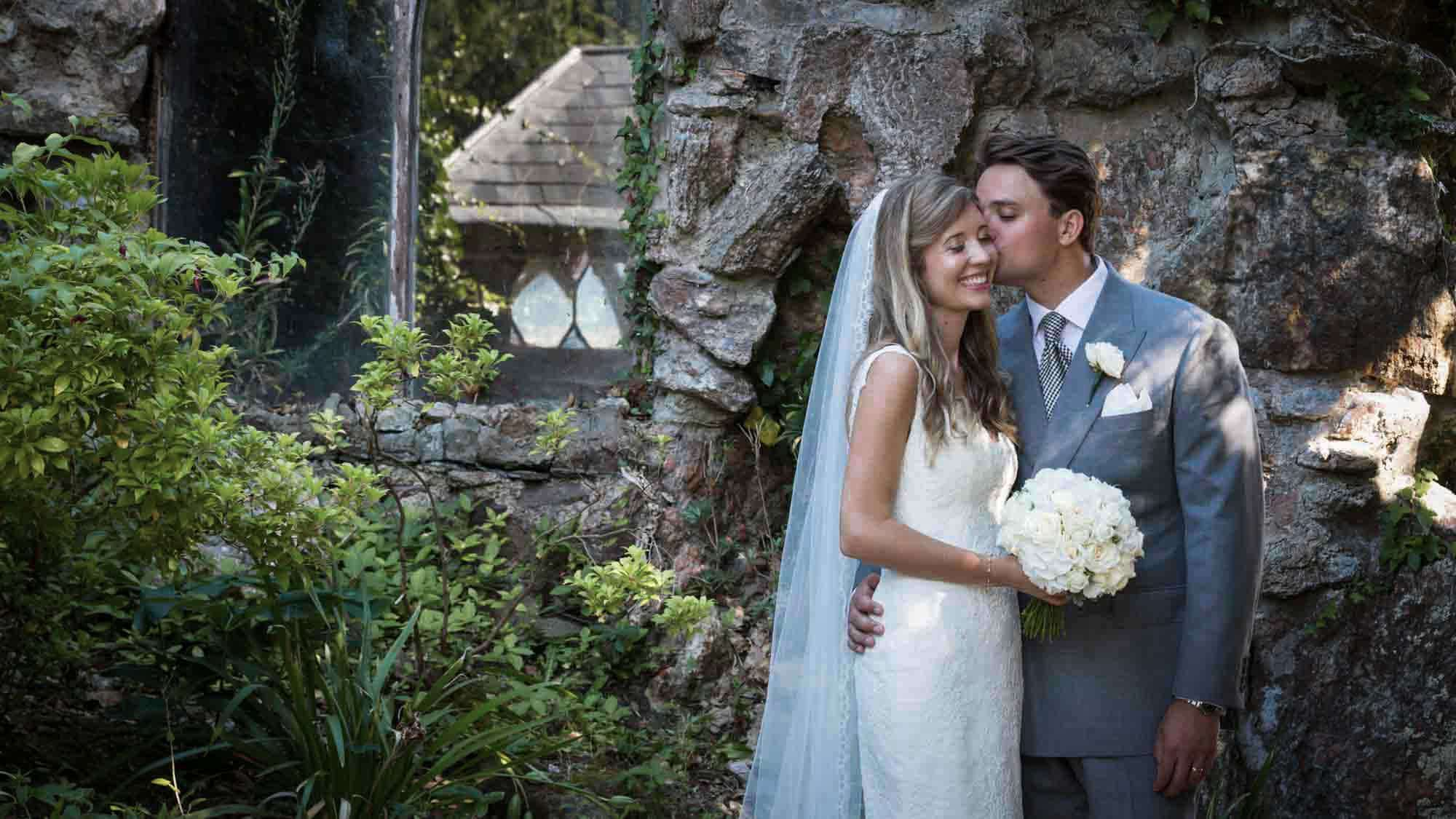Bride and groom kiss in gardens at St Audries Park