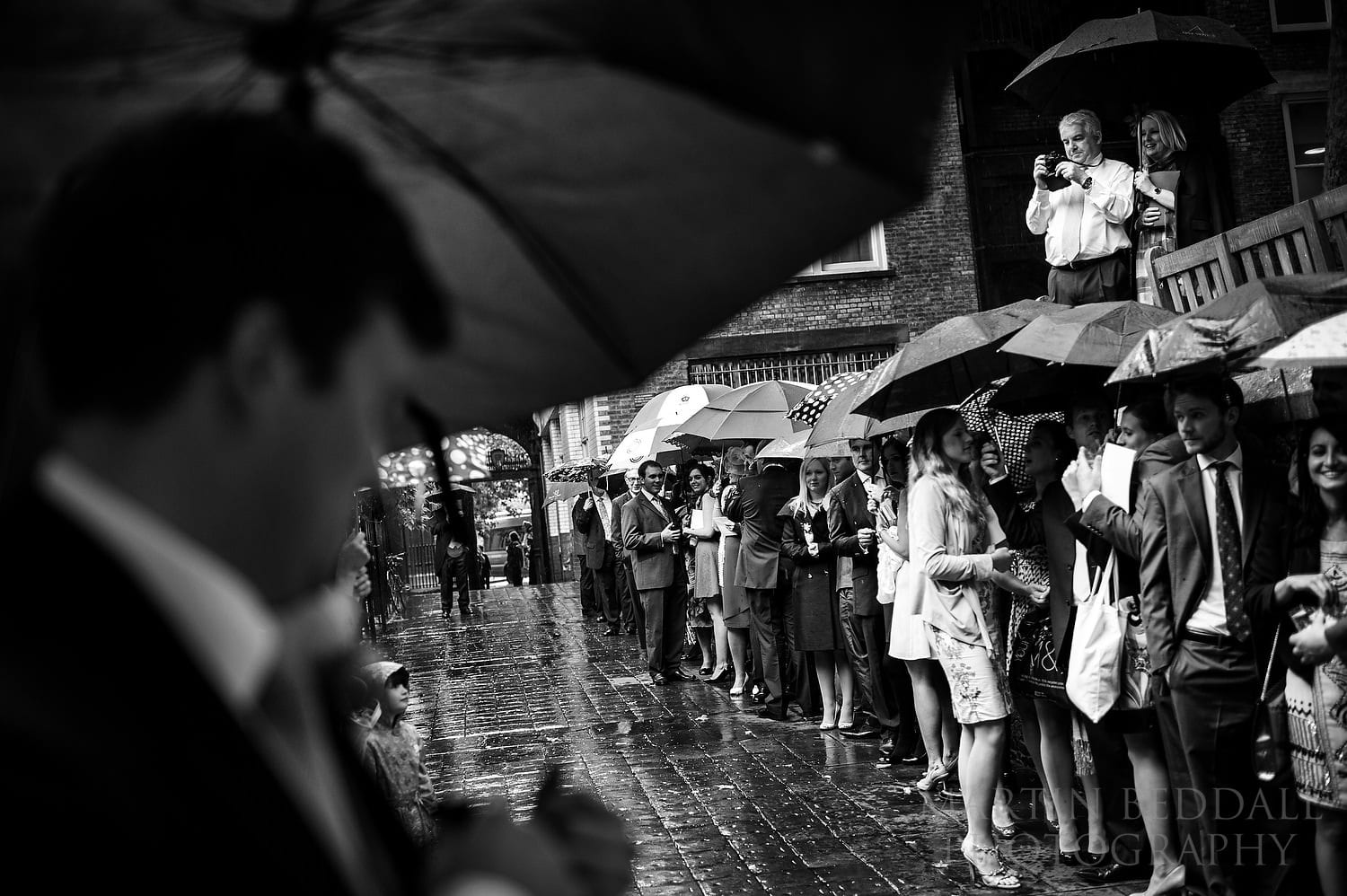 Wedding guests wait in the rain