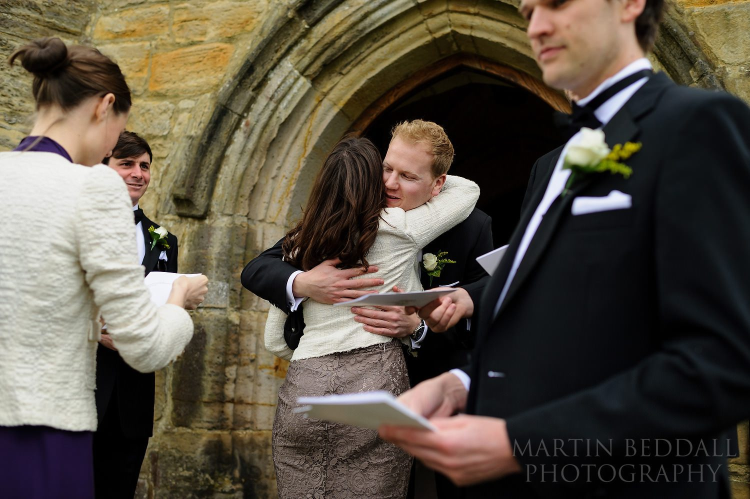 Groom greeting wedding guests outside the church