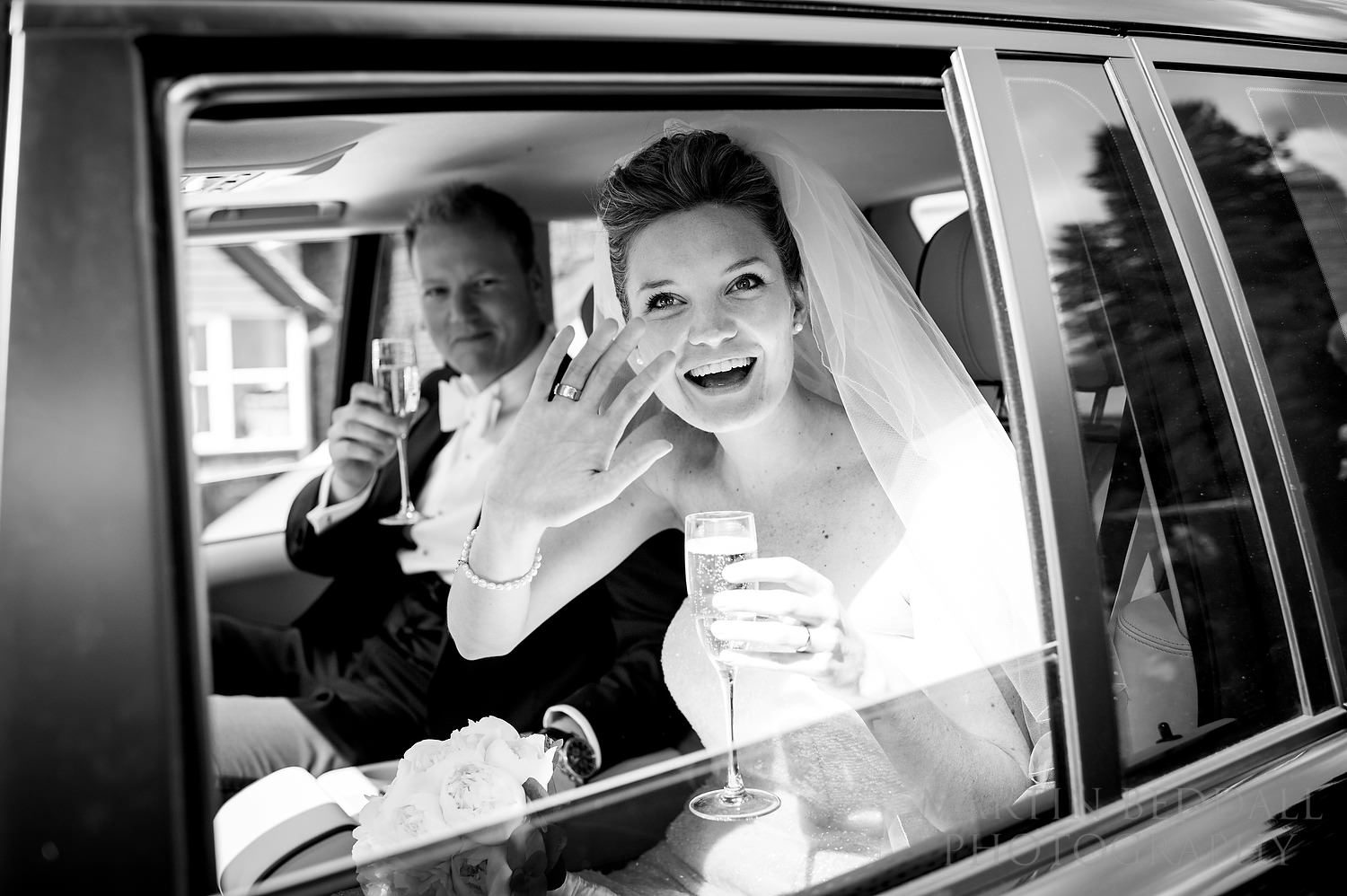 Waving from the wedding car