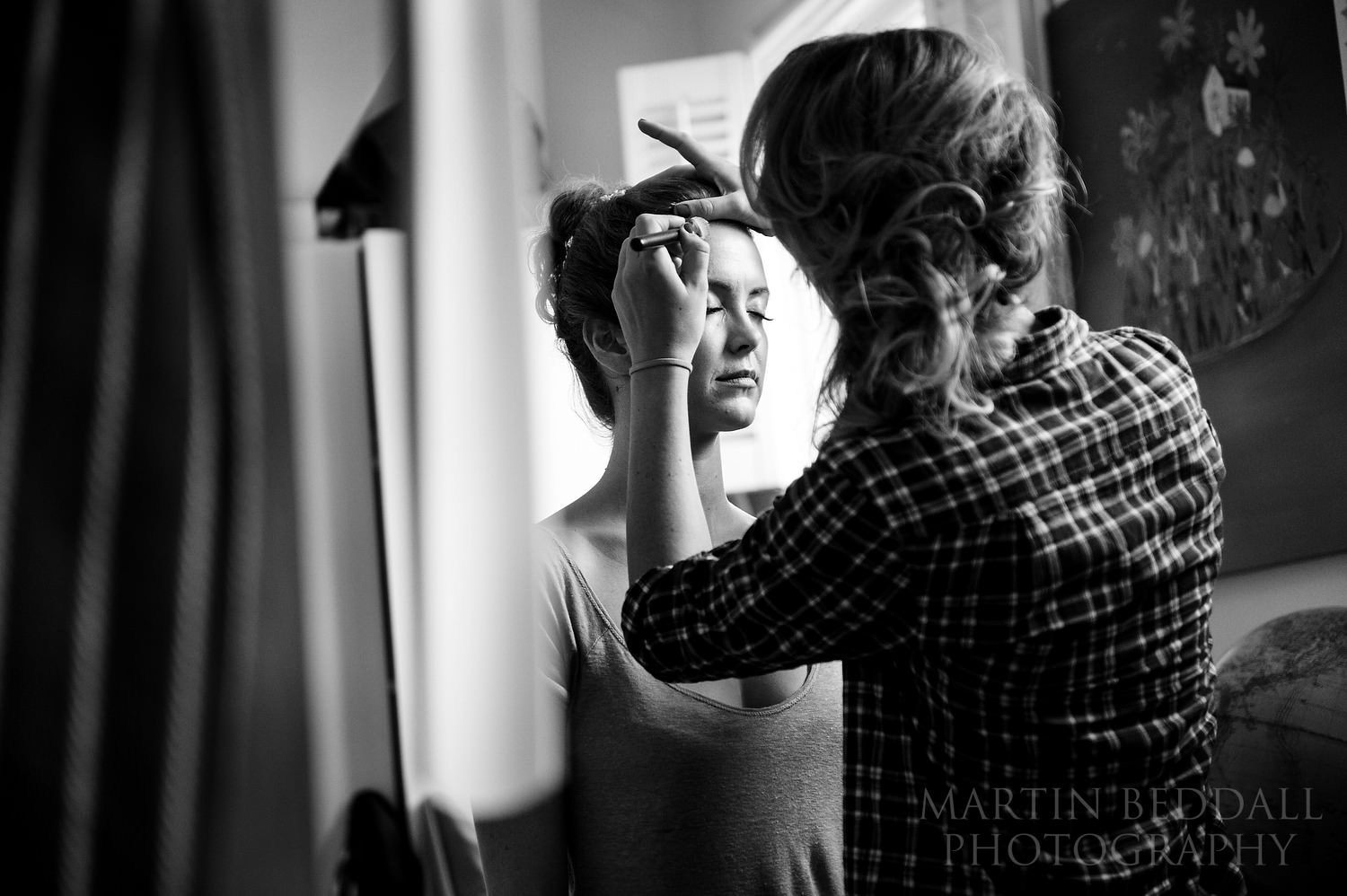 Bride's sister applies her makeup for her
