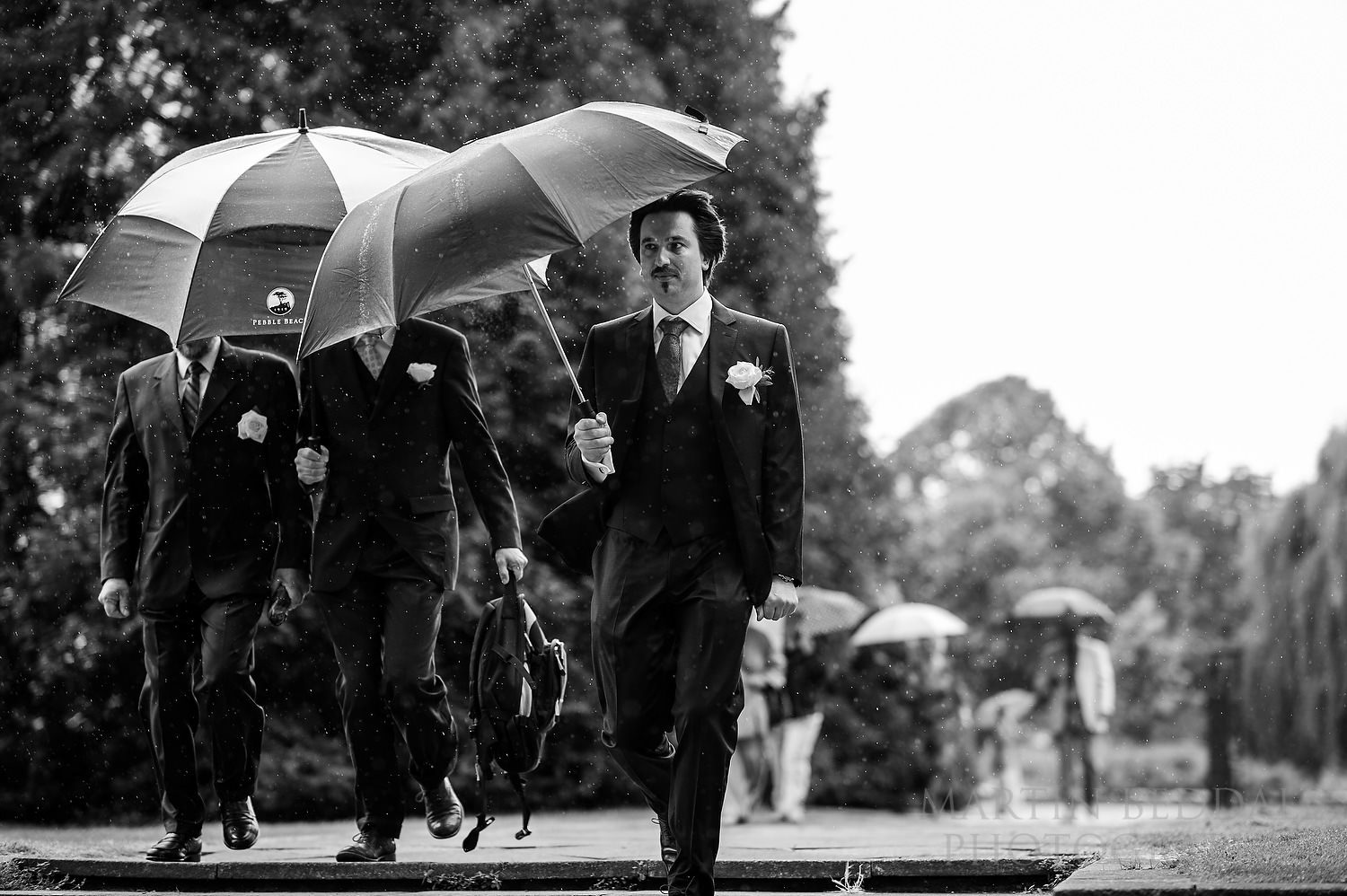 Groom arrives in the rain at Pershore Abbey