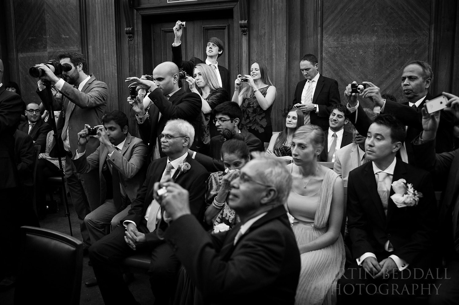 Wedding guests photograph the couple