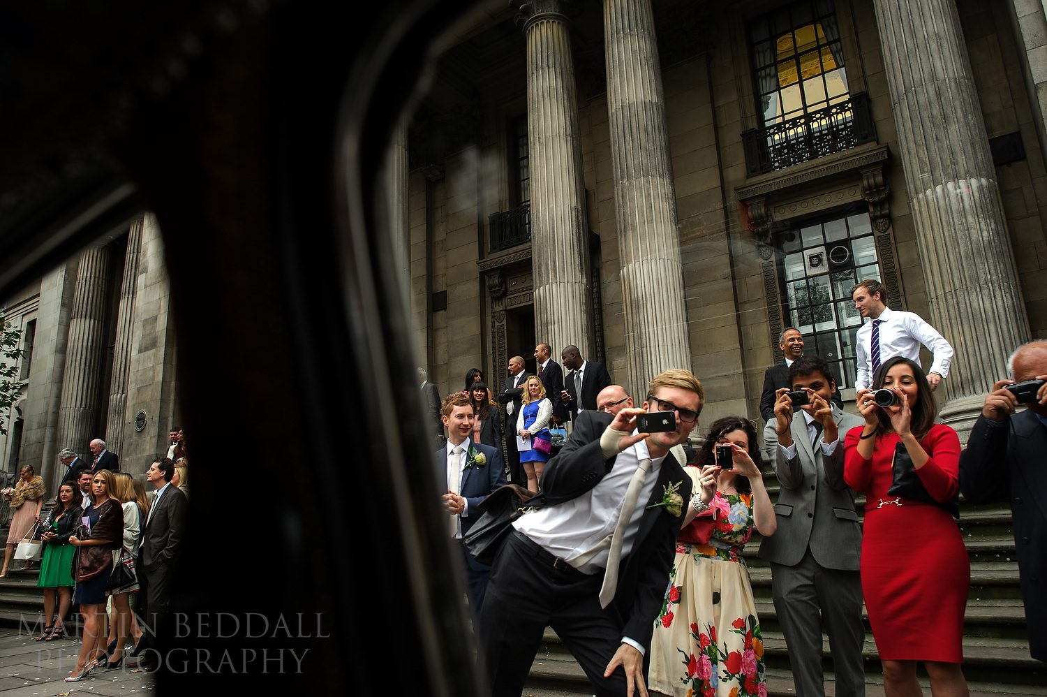 Guests see off the couple in their wedding car